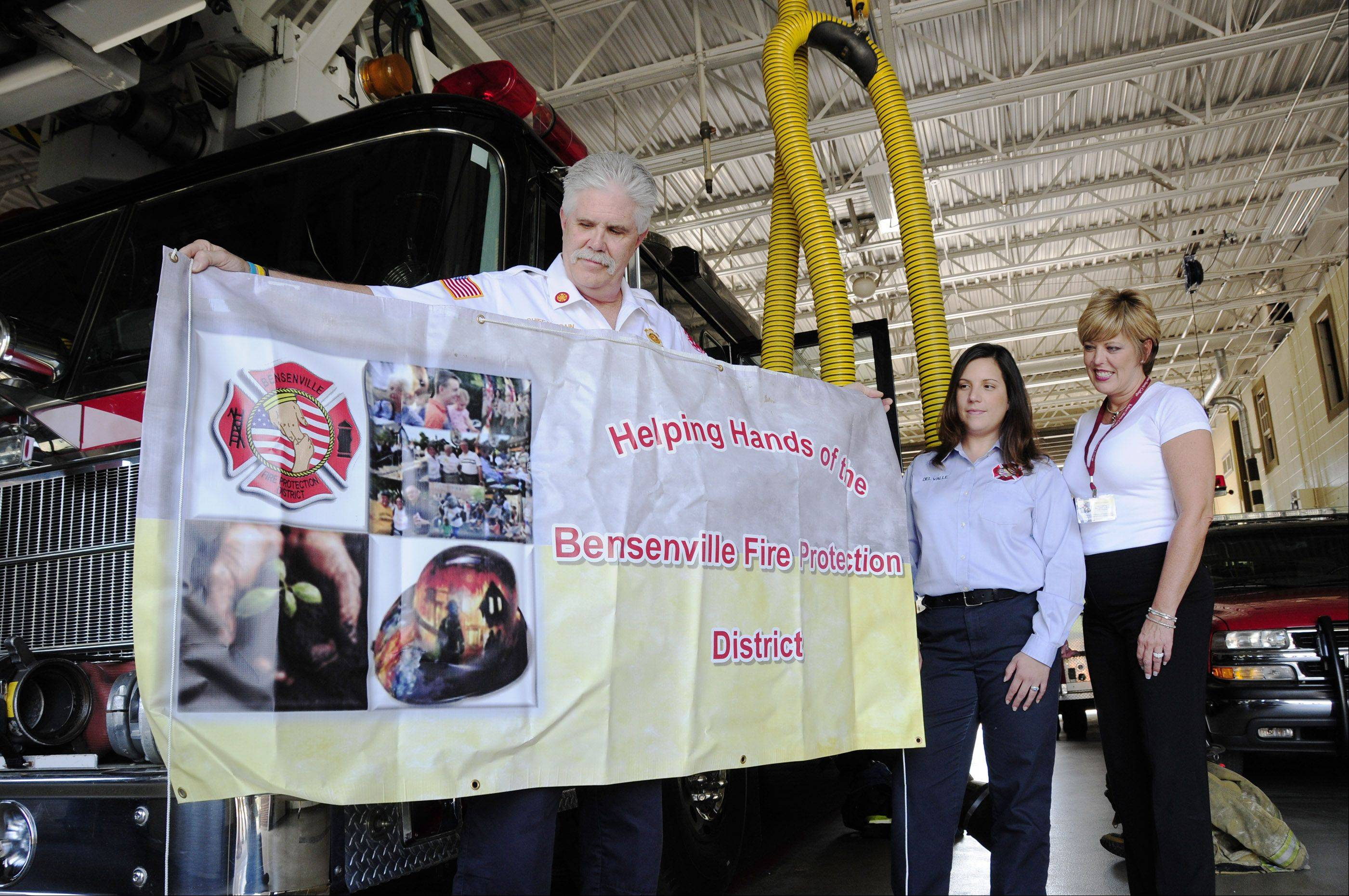 Bensenville Fire Chief Mike Spain displays the department�s Helping Hands banner along with the group�s Executive Director Liz Delvalle and President Denise Gallagher. Helping Hands is a volunteer organization that aims to help fire victims with food, clothing and comfort.