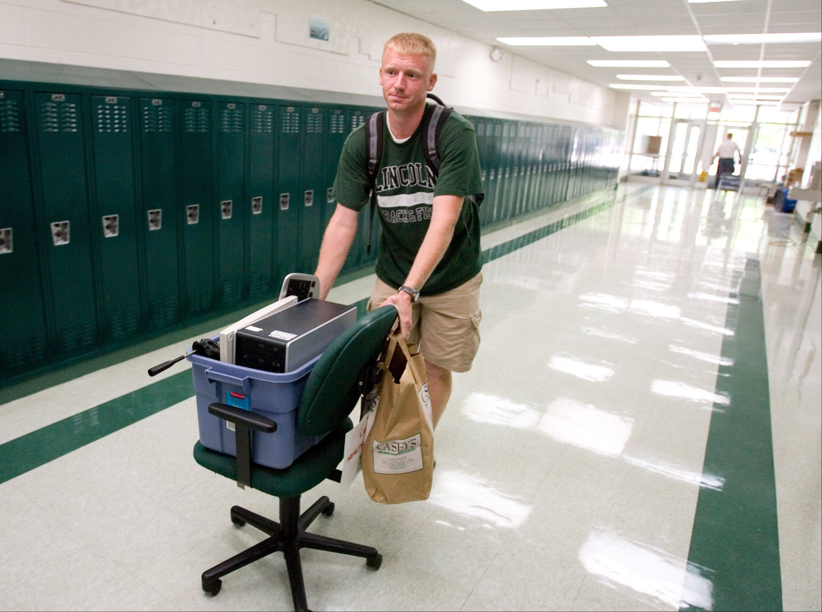 Josh Stumpenhorst, a big believer in the use of technology as a learning tool, moves equipment into his sixth-grade classroom at Lincoln Junior High in Naperville to get ready for the school year.