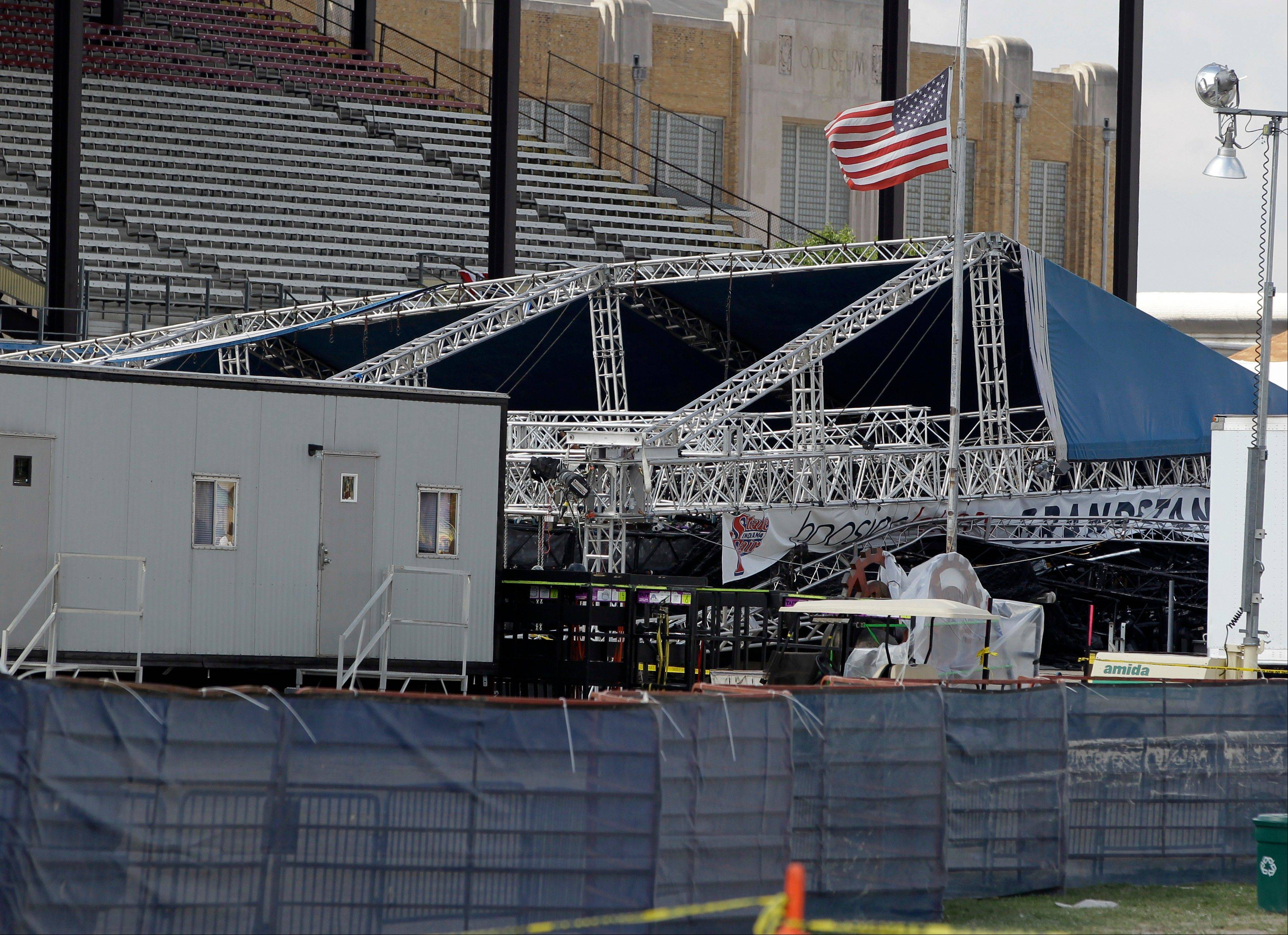A flag flies at half-staff near the collapsed stage Indiana State Fair in Indianapolis where five people were killed Saturday night in the accident.