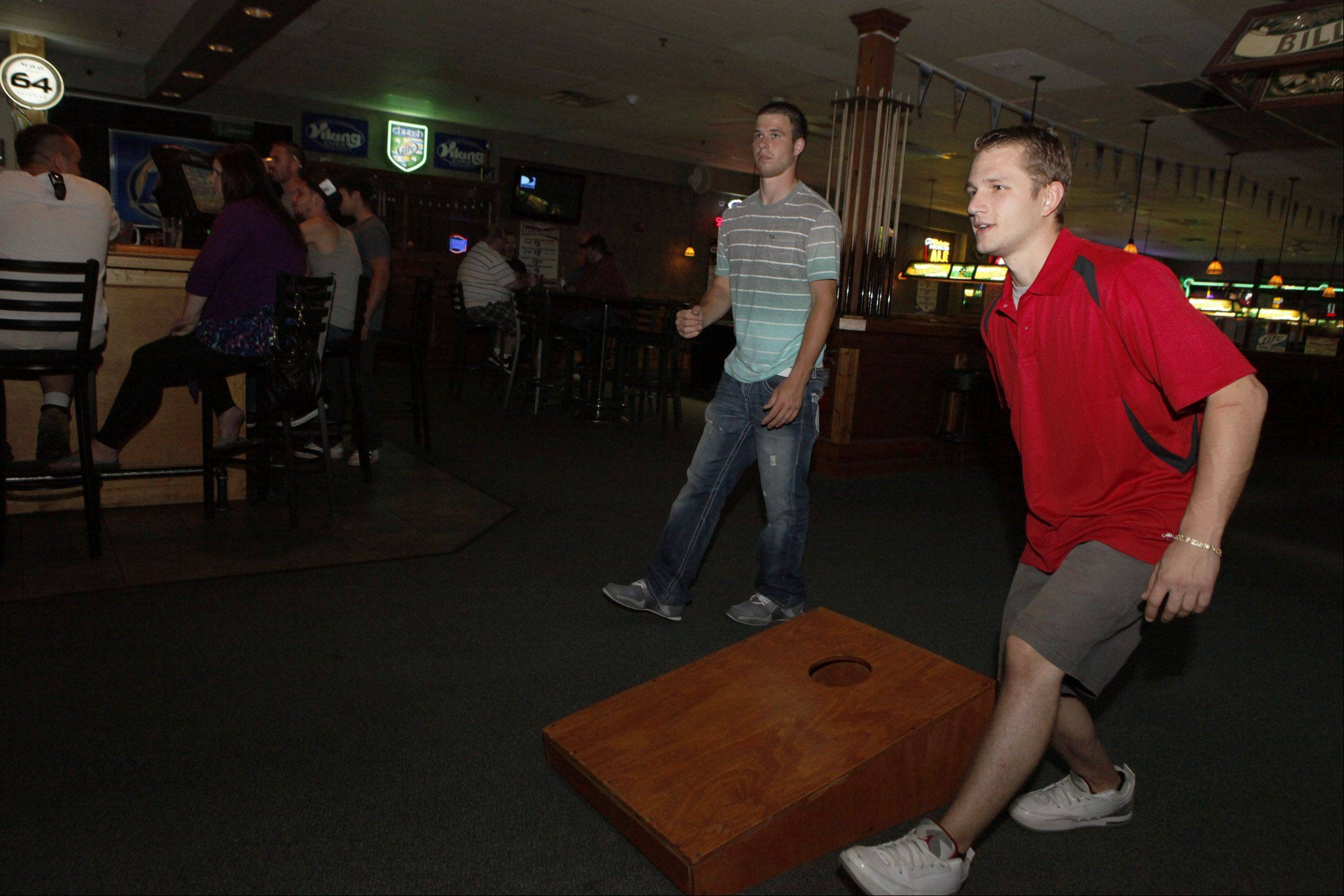 Matt Tagney and Kyle Jendra play a game of bags inside Q Sports Bar in Downers Grove.