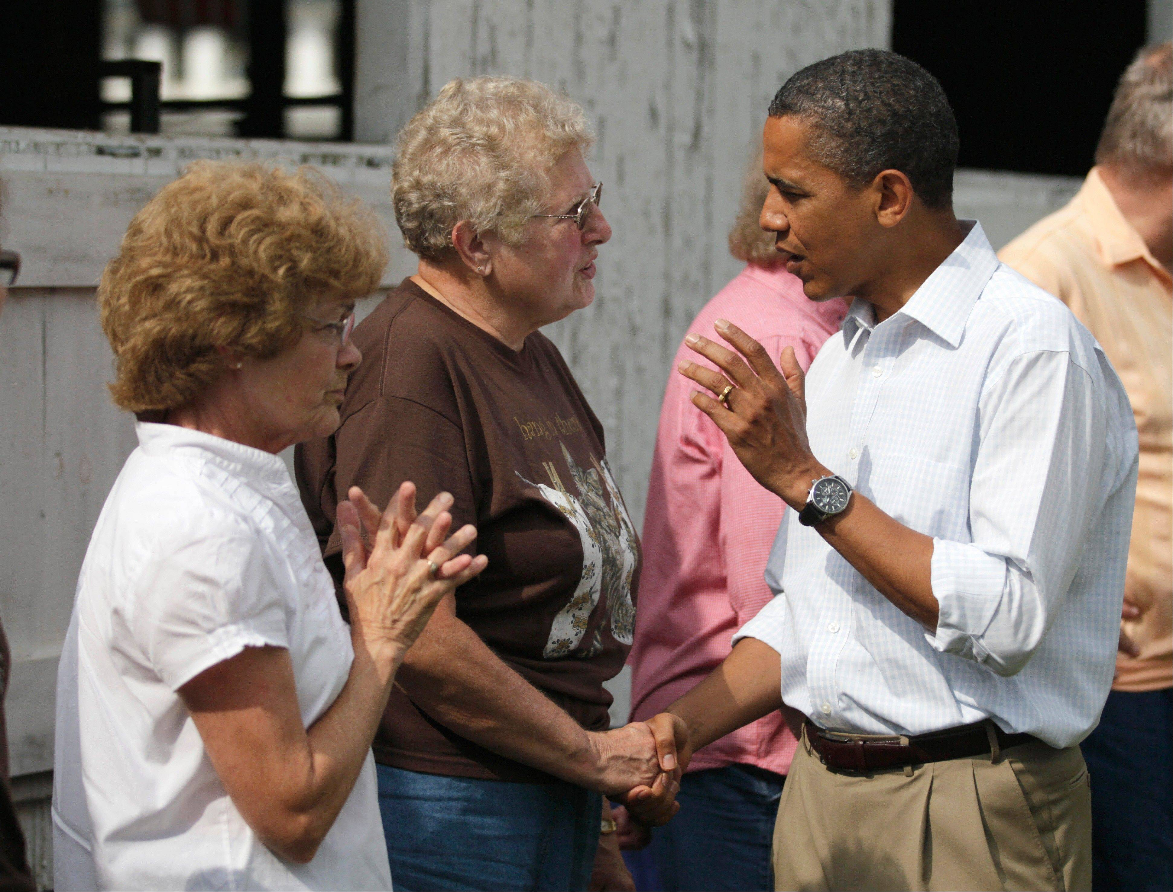 President Barack Obama visits with Norma Haan, 68, center at the Whiteside County Fair, Wednesday, Aug. 17, 2011, in Morrison, Ill.