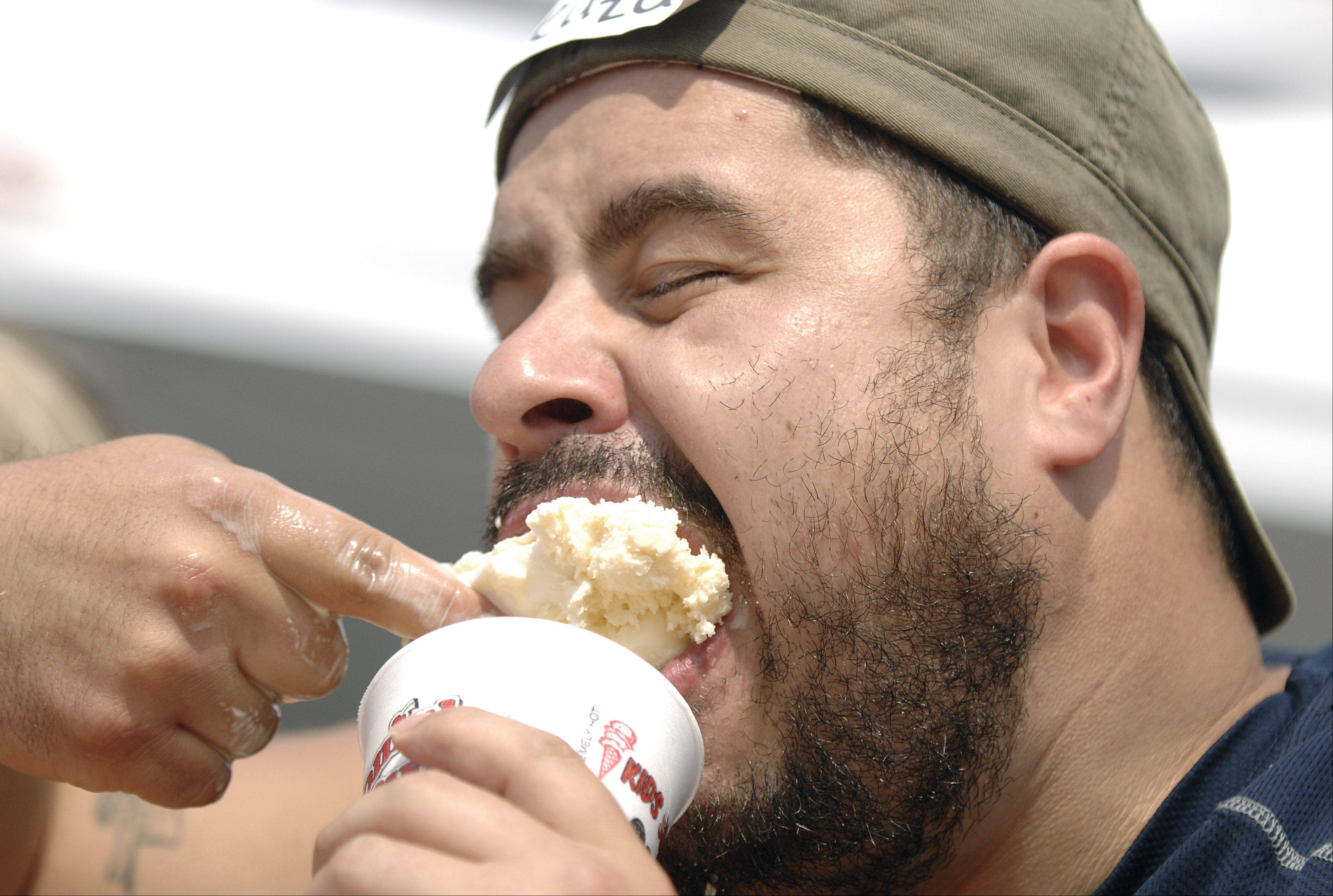 Eleazav Cervanantes of Elgin shovels down eight cups of vanilla ice cream to win the adult category in the Colonial Cafe ice cream eating contest at South Elgin's Riverfest Express. This was his first ice cream eating contest.