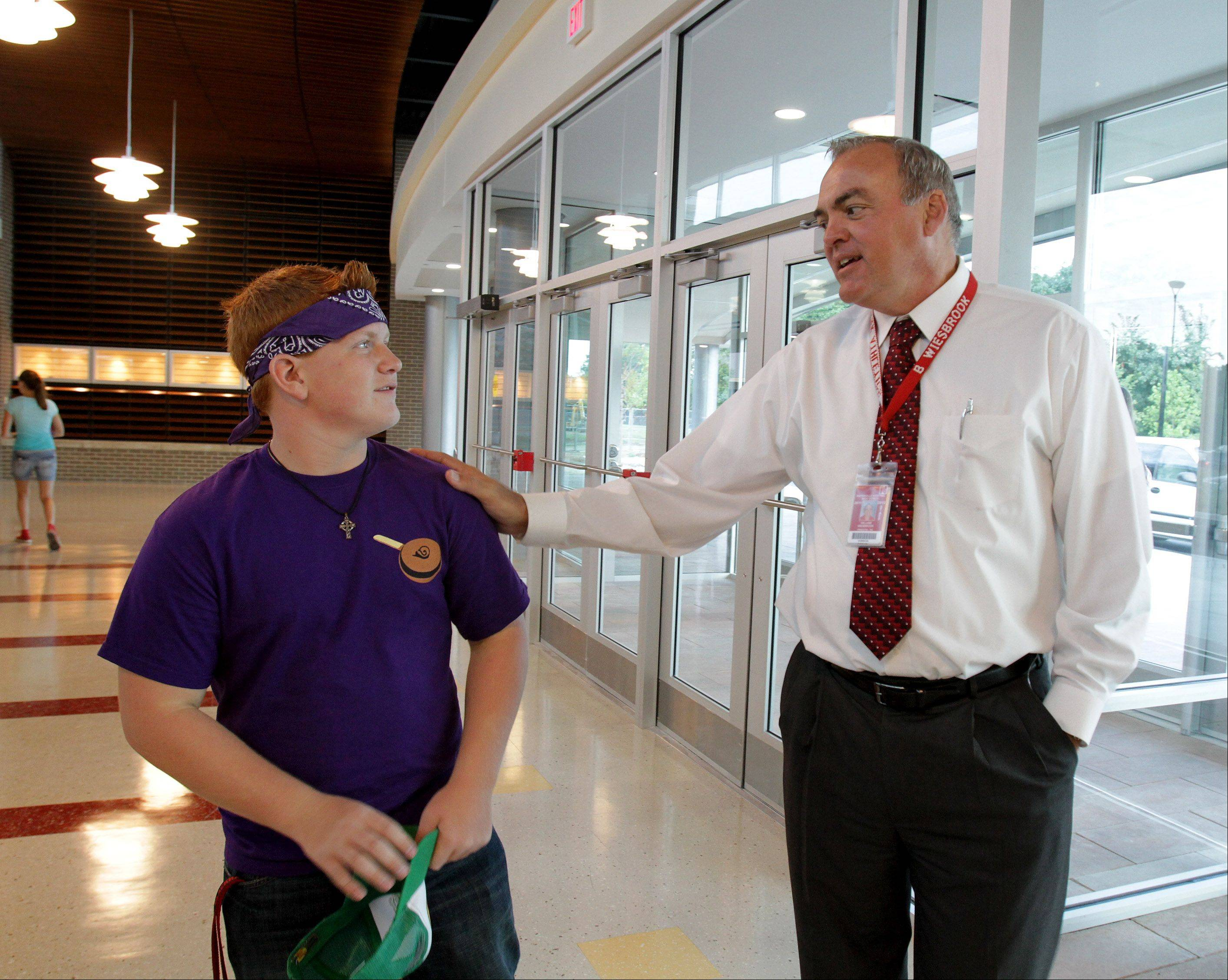 Principal Bill Wiesbrook greets junior Justin Tardy on the first day of school Wednesday in the fully renovated Naperville Central High School.