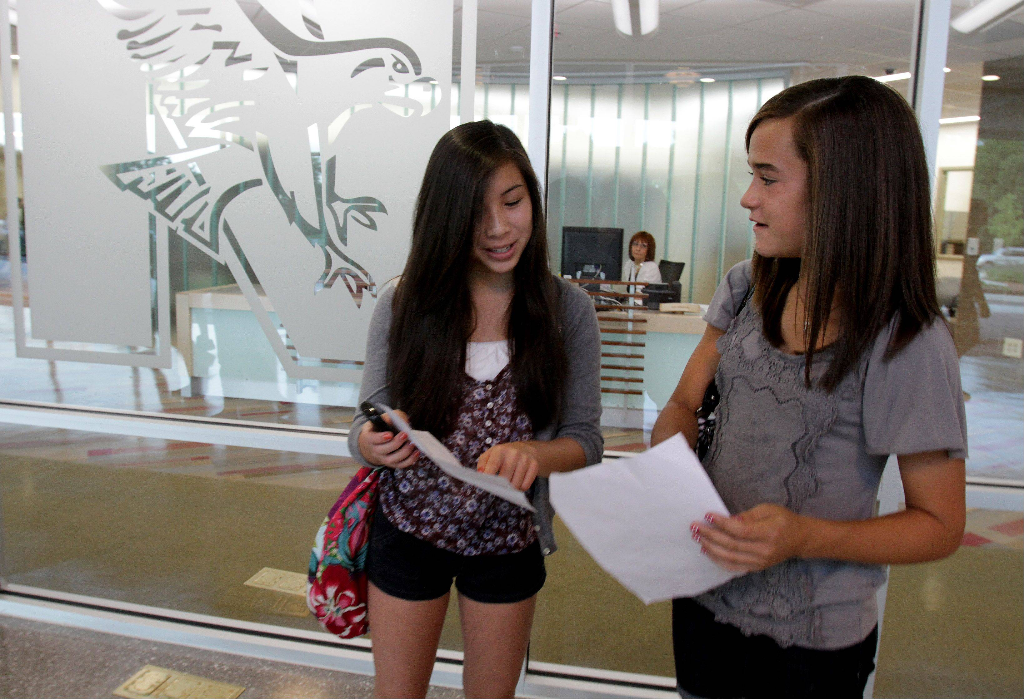 Freshman Mariel Singson and Katie Lamich look over their schedule during the first day of school in the fully renovated Naperville Central High School.