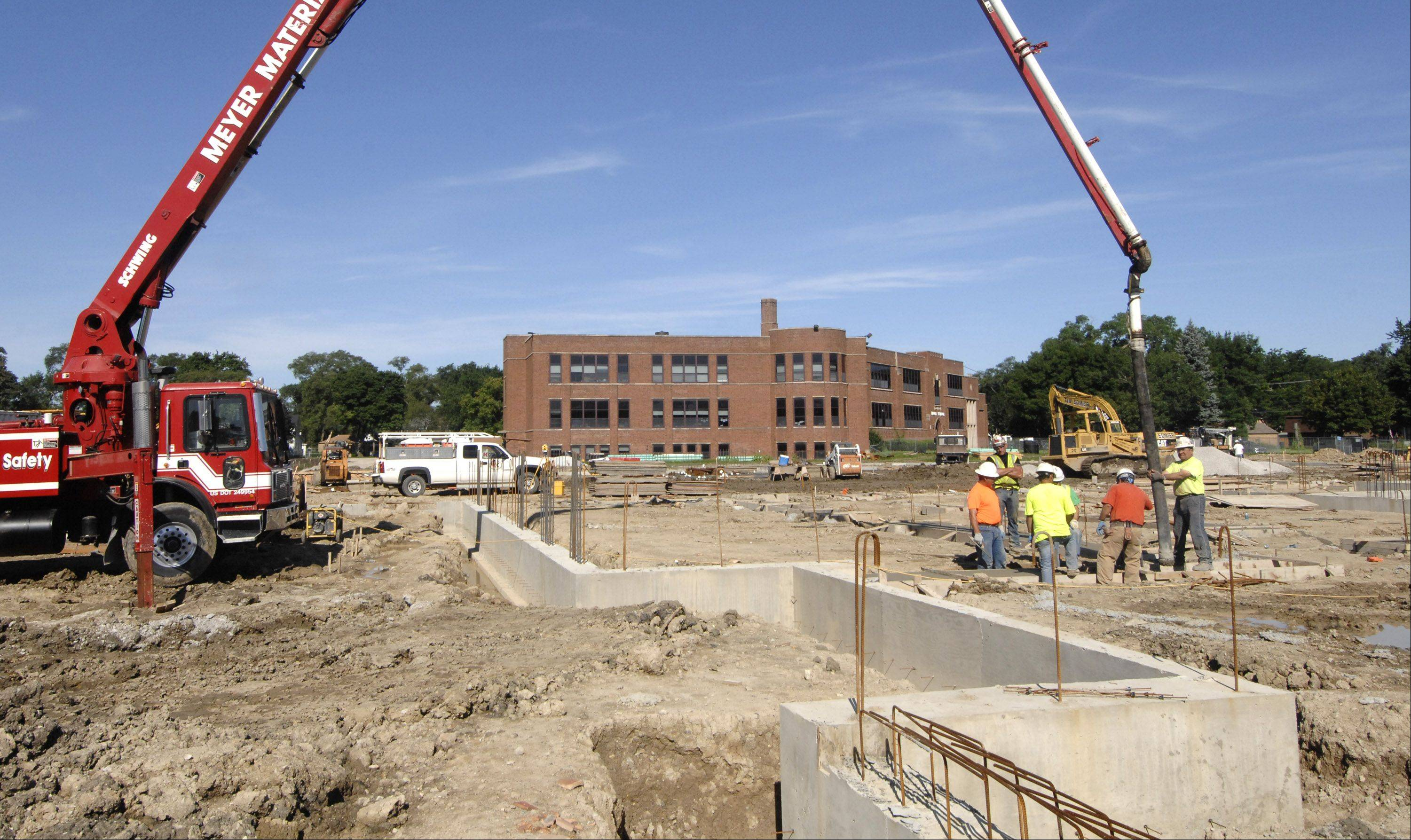 Workers pour concrete for the foundation of the addition to Tioga school in Bensenville. District 2 is working to consolidate its four schools into two.
