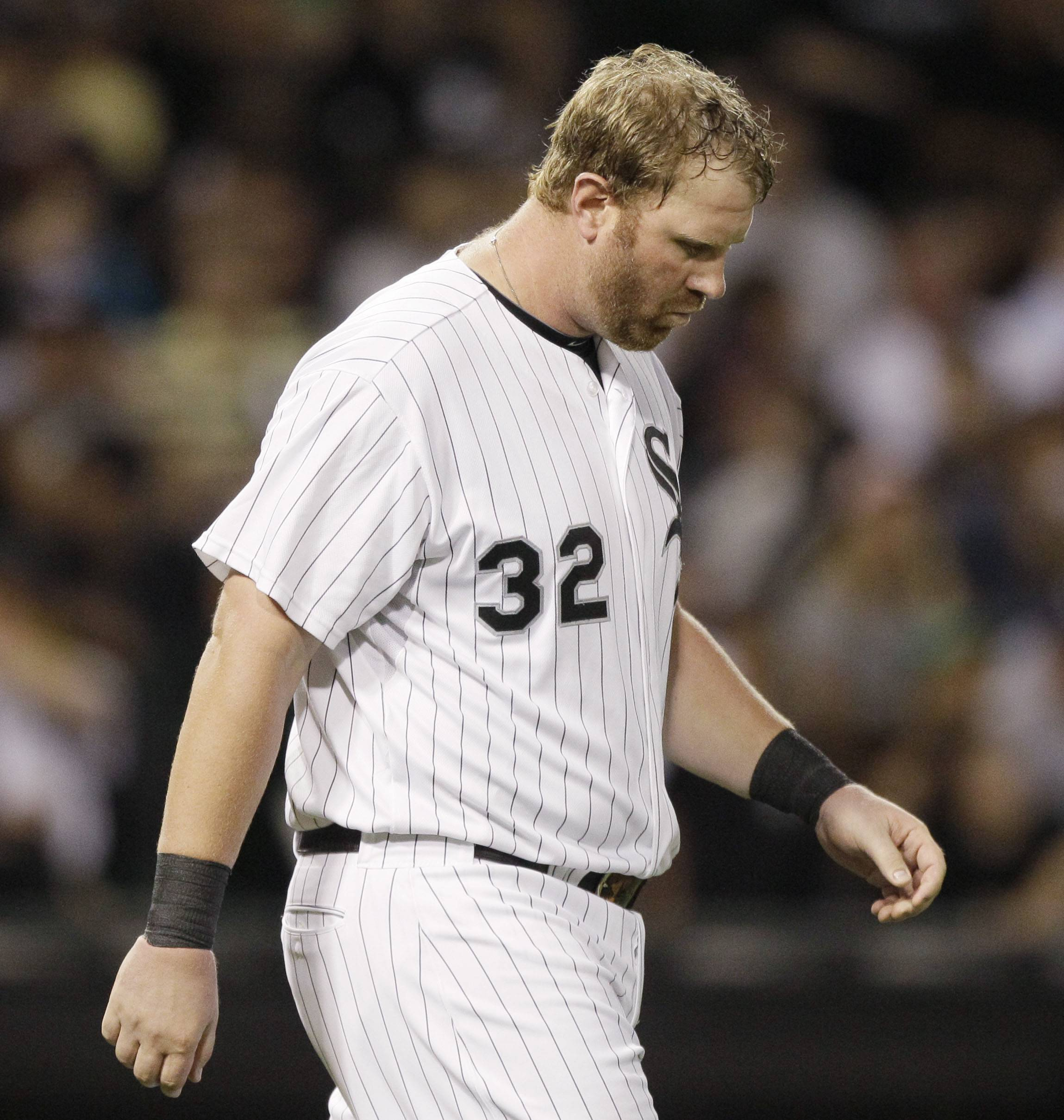 Adam Dunn looks down as he walks on the field after striking out during the fifth inning Thursday night at U.S. Cellular Field.