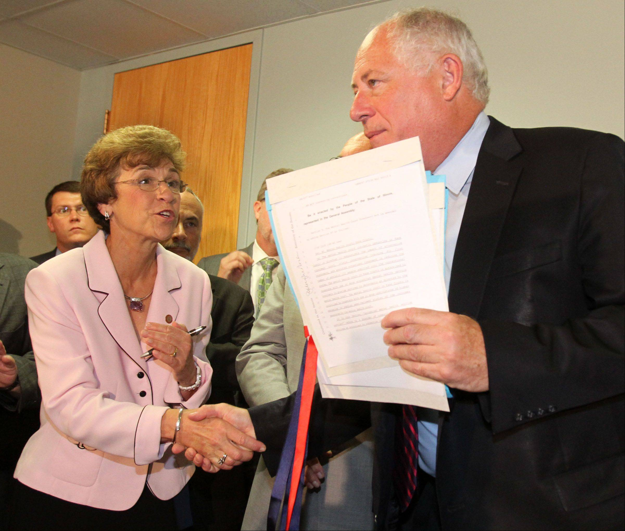 Arlington Heights Village President Arlene Mulder congratulates Gov. Pat Quinn Thursday after he signs new mental health legislation at Alexian Brothers Center for Mental Health in Arlington Heights. The legislation creates a task force to study how to improve access to mental health services.
