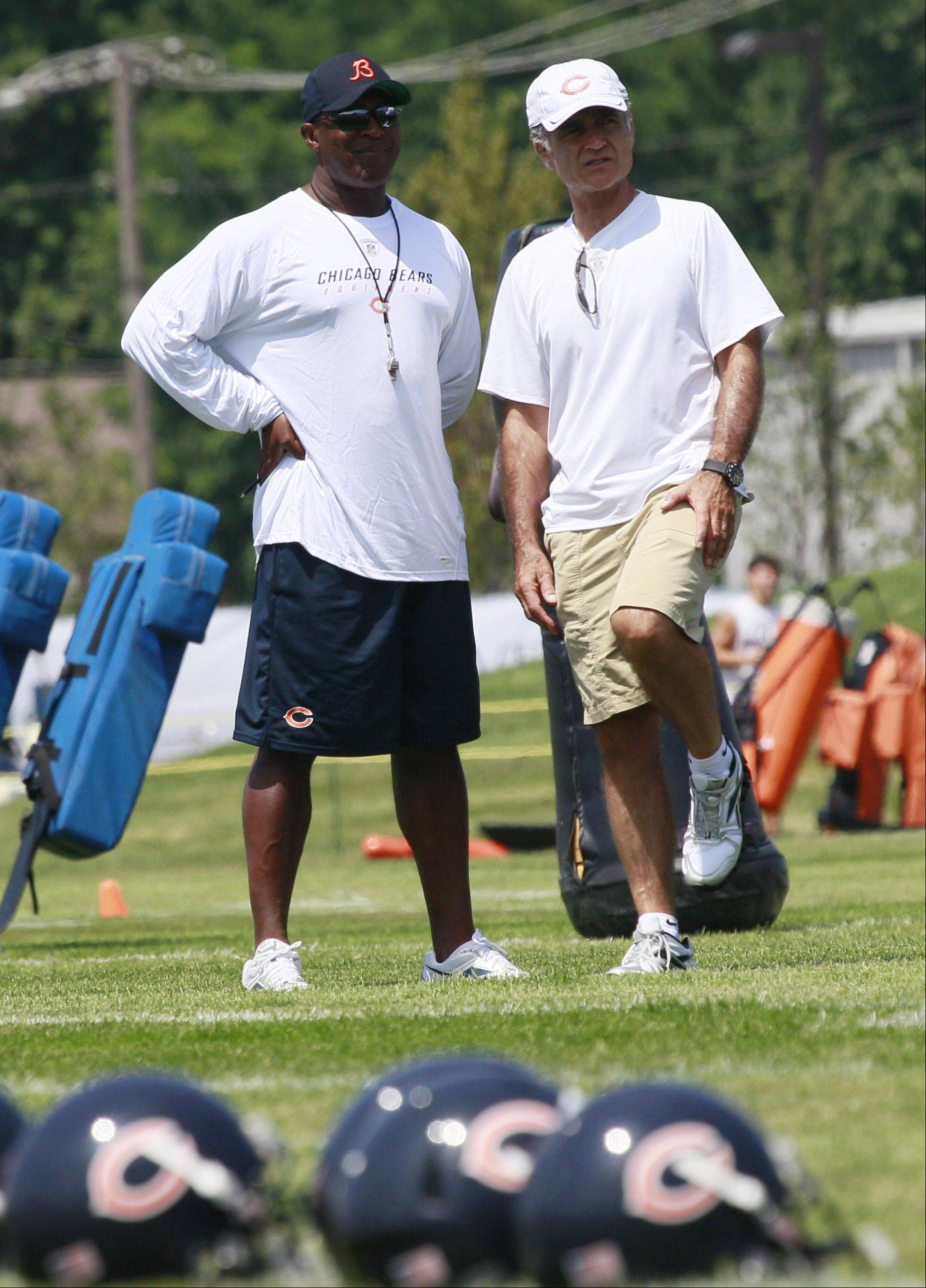 Bears general manager Jerry Angelo, right, talks with head coach Lovie Smith during NFL football training camp on Sunday, July 31, 2011, at Olivet Nazarene University in Bourbonnais.