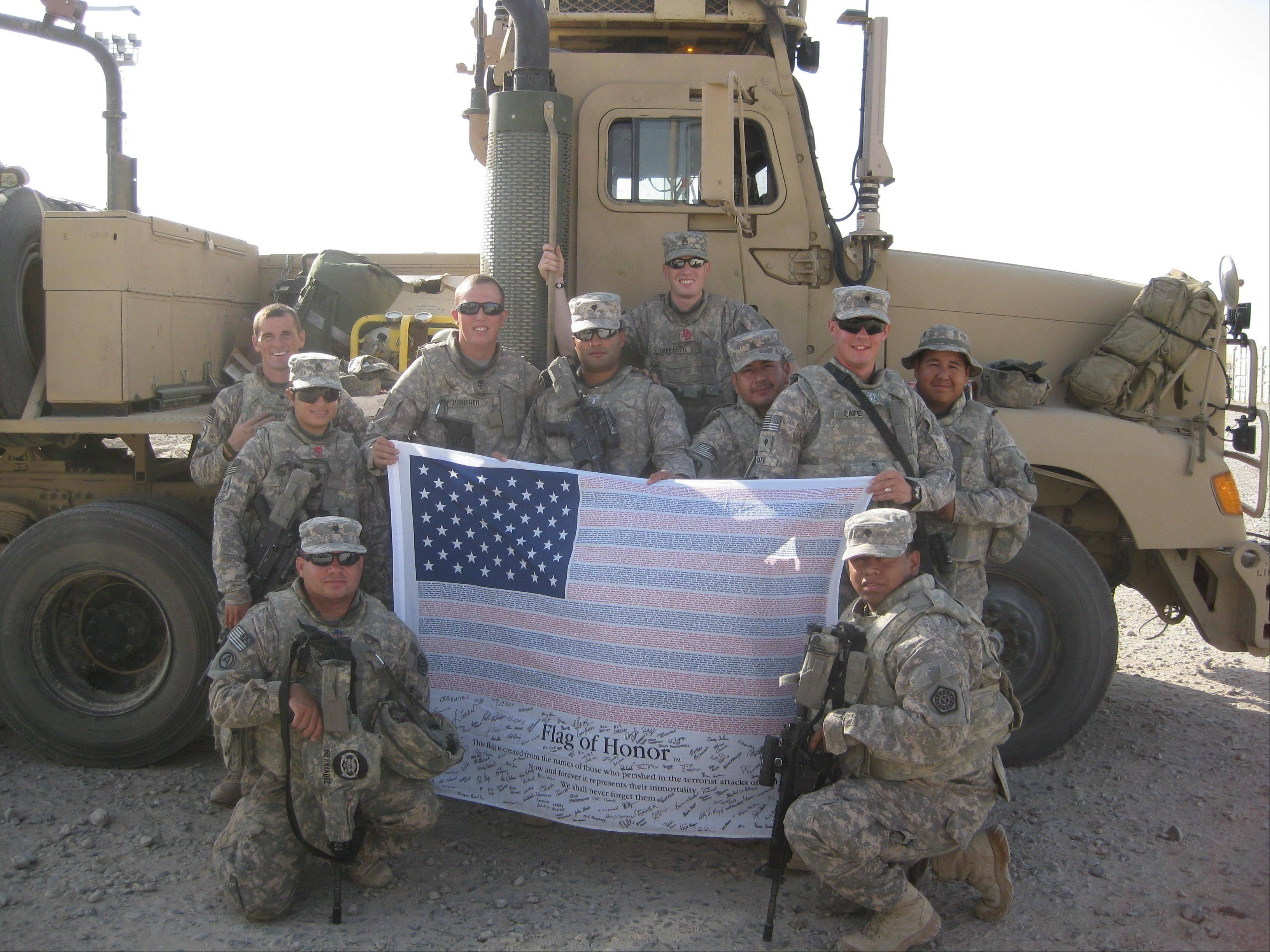 Members of the 1244th Transportation Company of the Illinois Army National Guard, including Hanover Park residents Adam Smith, fourth from left, wearing no hat, and Juan Millan, farthest right, standing, hold a flag signed by Hanover Park staff and officials while in Baghdad, Iraq. The photo will hang in the village hall lobby.