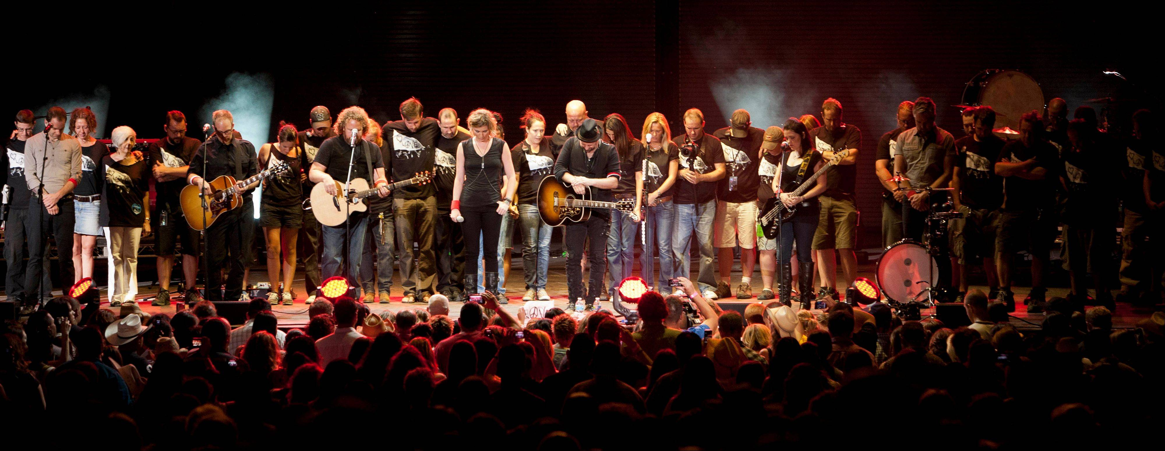 Sugarland duo Jennifer Nettles, middle left, and Kristian Bush, middle right, along with the rest of the tour crew pause for a moment of silence Thursday night in Albuquerque, N.M., for victims of the stage collapse at the Indiana State Fair that killed six people.