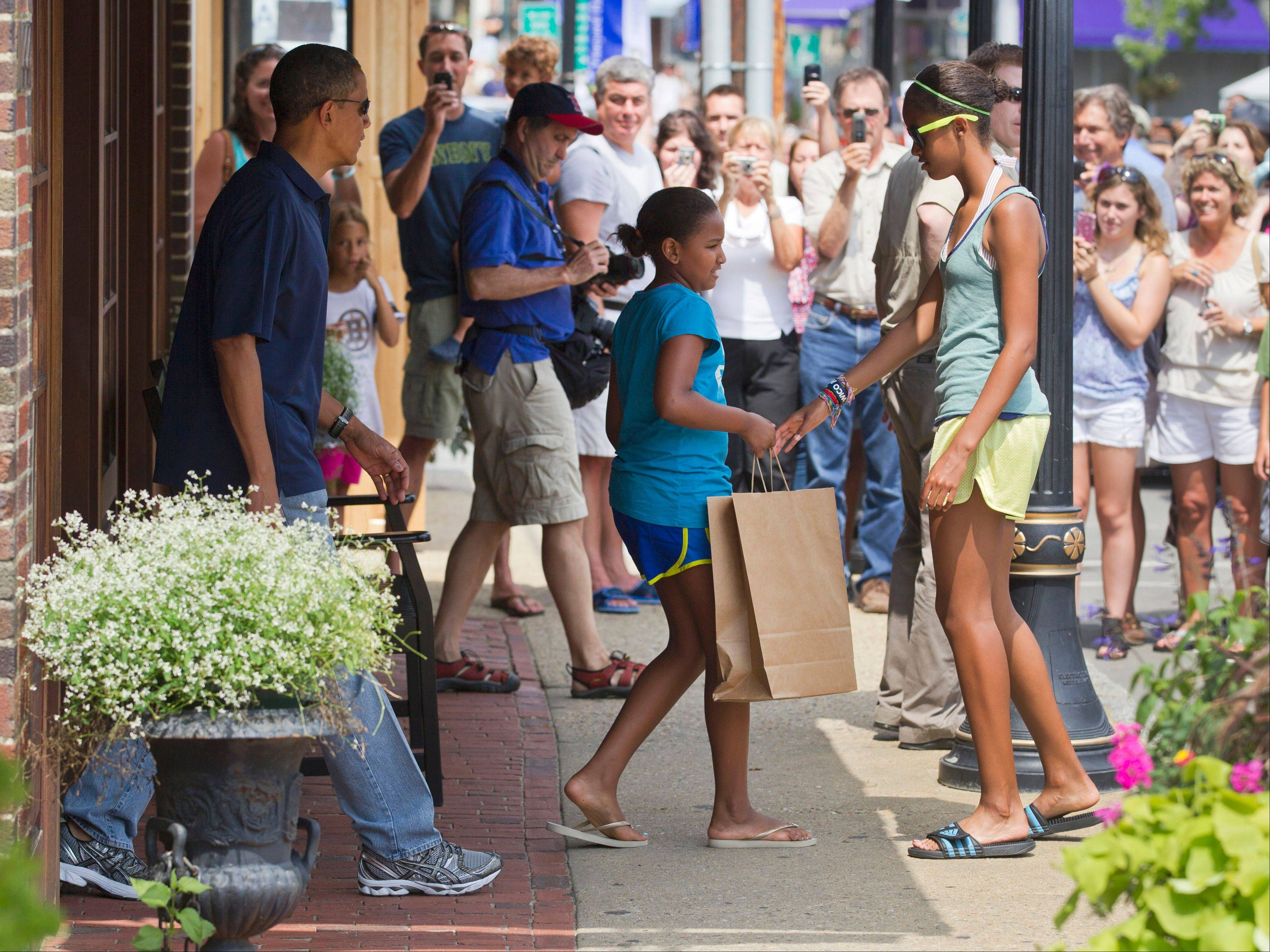 President Barack Obama, with his daughters Malia, right, and Sasha, center, leave the Bunch of Grapes book store Friday in Vineyard Haven, Mass.