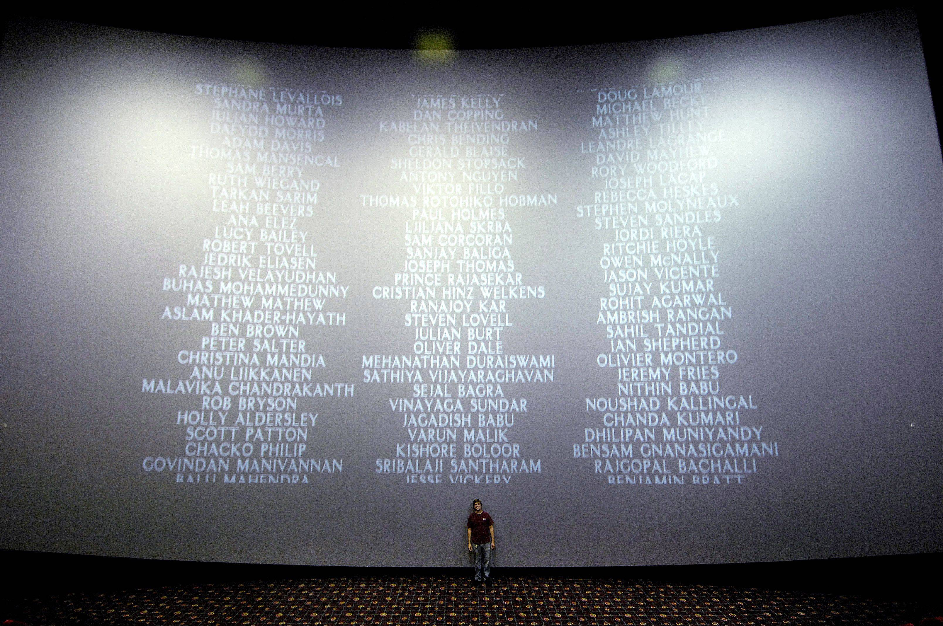 Paul Warren, IMAX/Projection manager at Randall 15 in Batavia, stands at the base of the 43' x 70' IMAX movie screen as credits roll for the latest Harry Potter movie.
