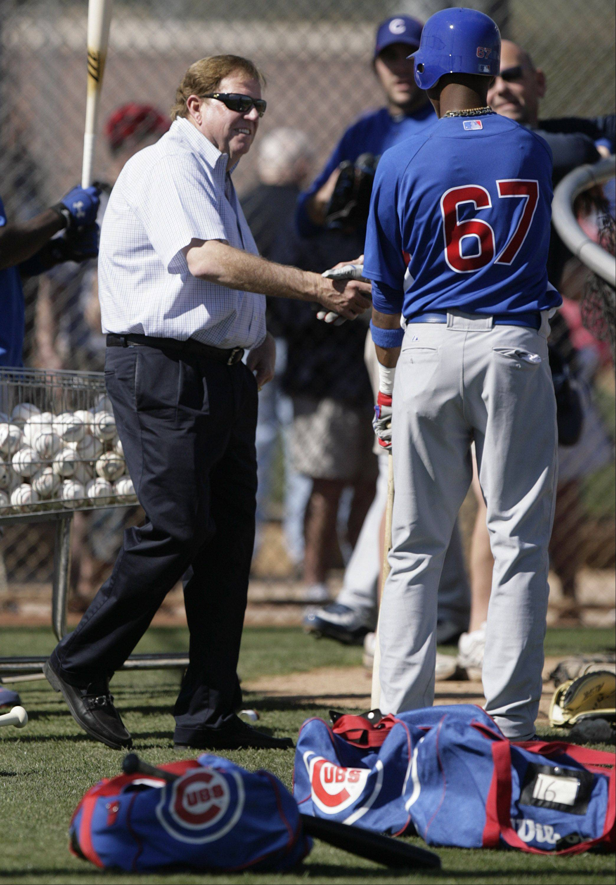 Chicago Cubs general manager Jim Hendry, left, shakes hands with infielder Starlin Castro, right, as Castro waits his turn to take batting practice at the team's spring training baseball facility Thursday, Feb. 25, 2010, in Mesa, Ariz.