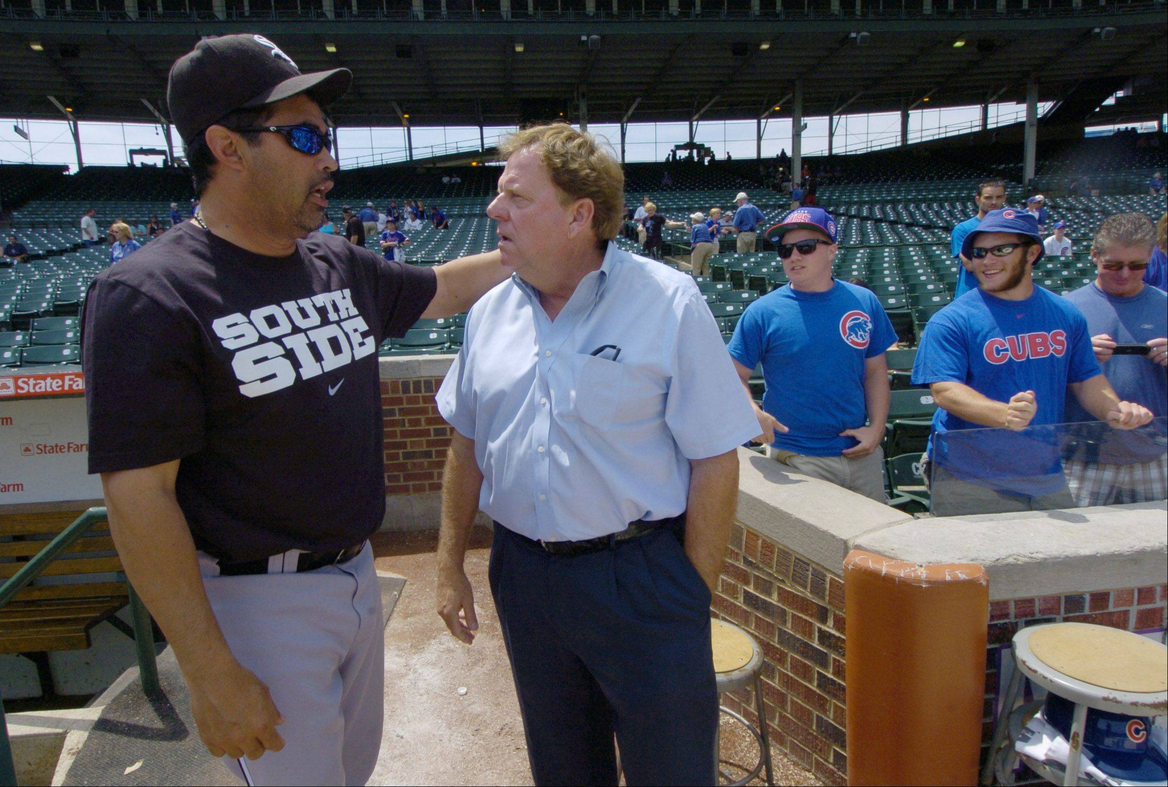 White Sox manager Ozzie Guillen talks with Cubs General Manager Jim Hendry before Sunday's game at Wrigley Field.