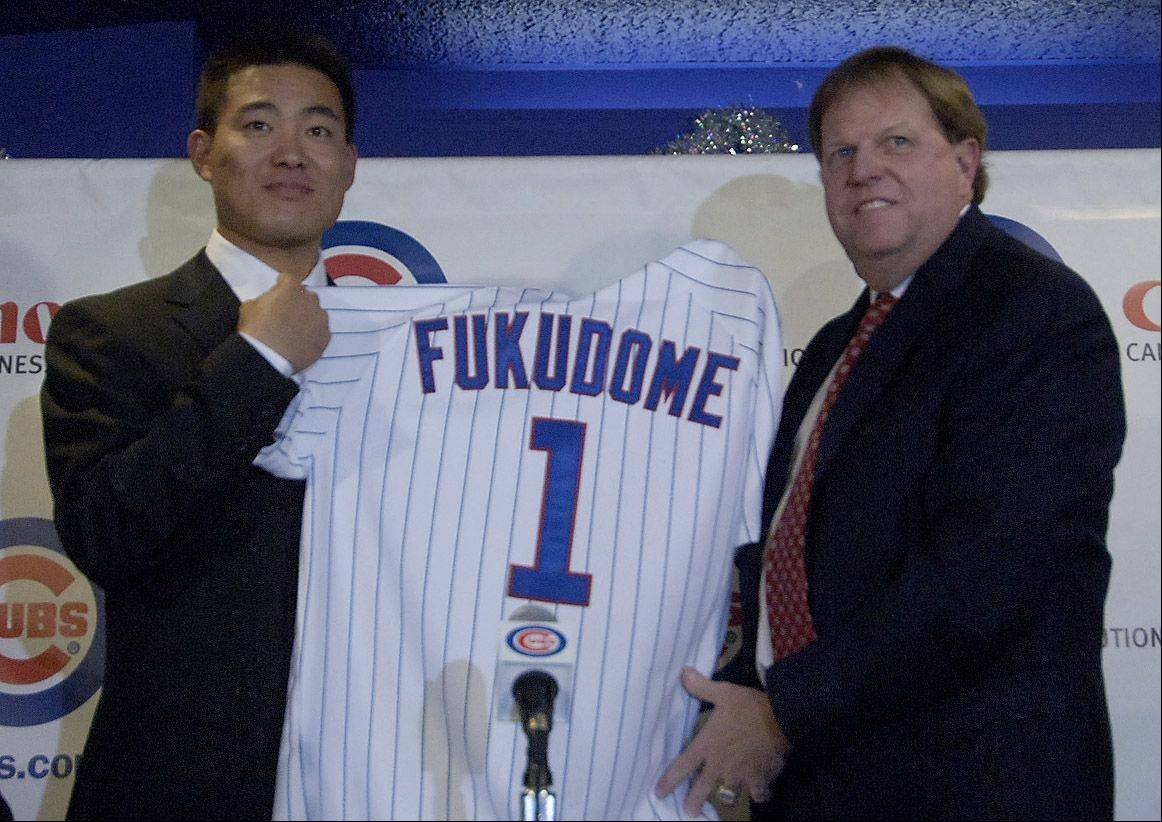 New Cub Kosuke Fukudome holds his jersey with Cubs Vice President and General Manager Jim Hendry during news conference at Wrigley Field.