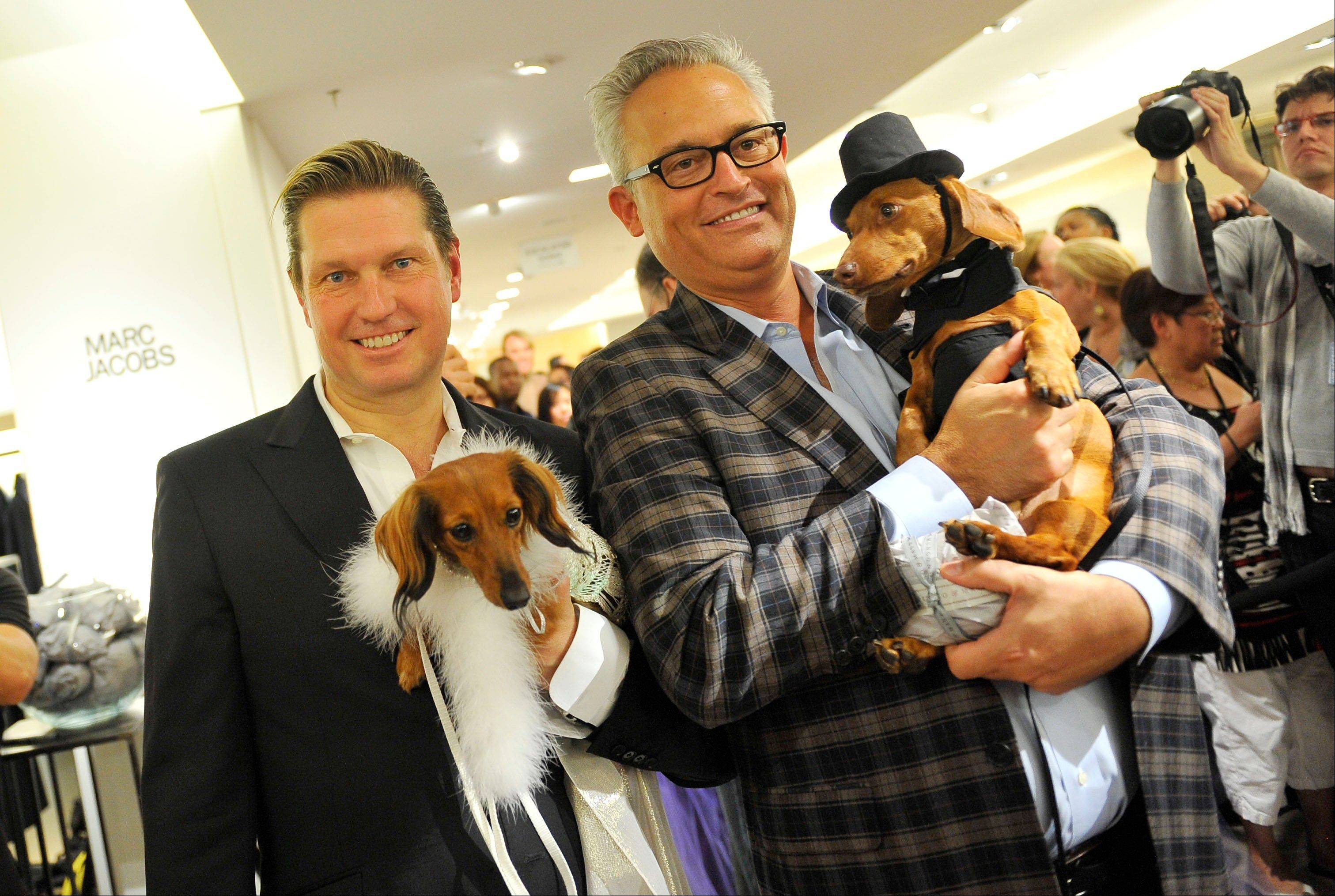 Designers Mark Badgley, left, and James Mischka hold their dogs Rommel and Whiskey during a doggie fashion show at Bergdorf Goodman during Fashion�s Night Out during Fashion Week in New York. the shopping initiative driven by Vogue Editor-In-Chief Anna Wintour, returns as a bigger event next month, extending to 250 U.S. cities, but there seems to be a sharper focus on industry stars — including designers, red carpet experts and makeup artists — instead of the Hollywood celebrities who grabbed headlines the past two years.