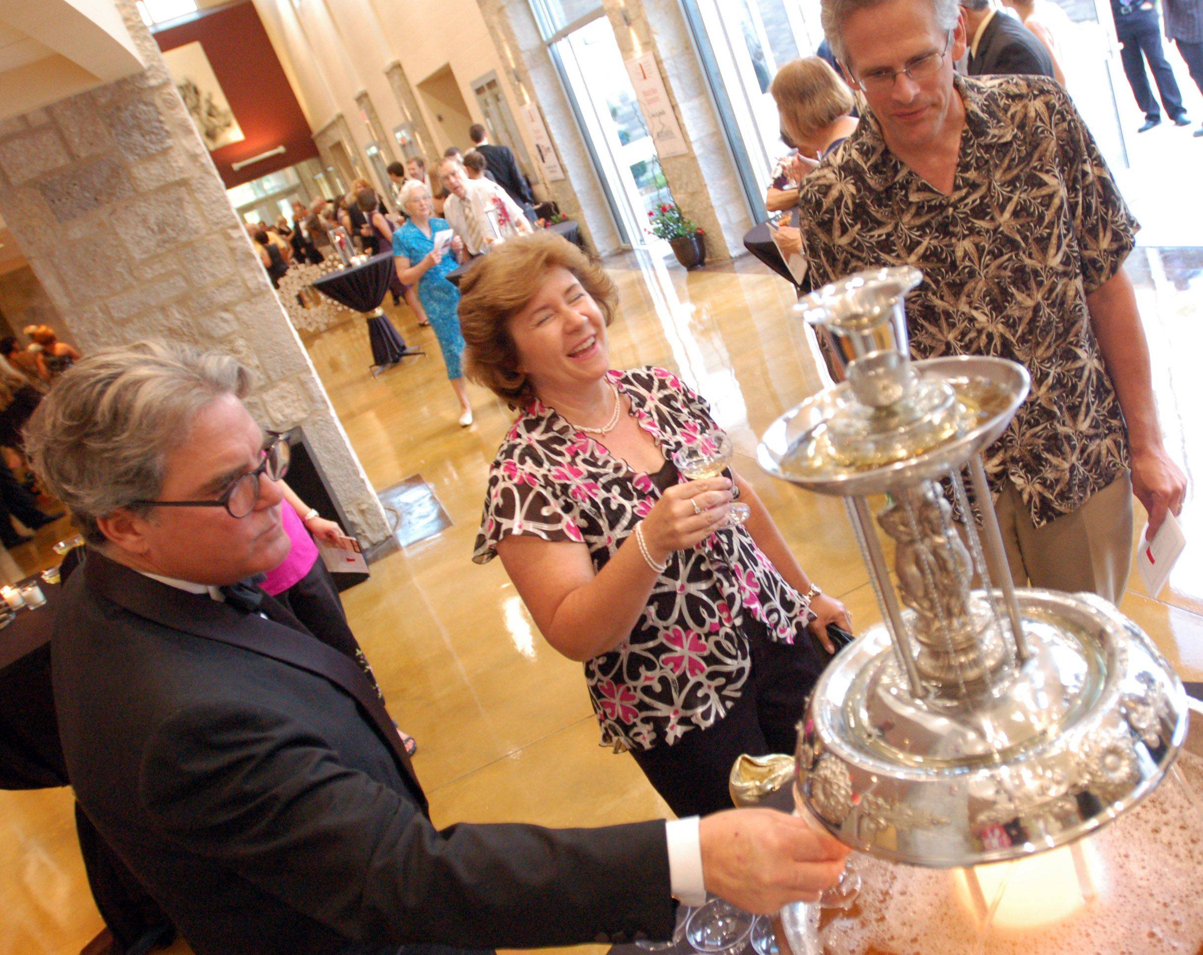 Vincent Gatto of Batavia, left, along with Stephanie Knappe, middle, and her husband, Ed Knappe, right, fill their glasses at the refreshment fountain, during the Batavia Fine Arts Centre�s Red Carpet Gala opening on Saturday. The arts center is the school�s first real auditorium, and will also serve as a community center for the city of Batavia.