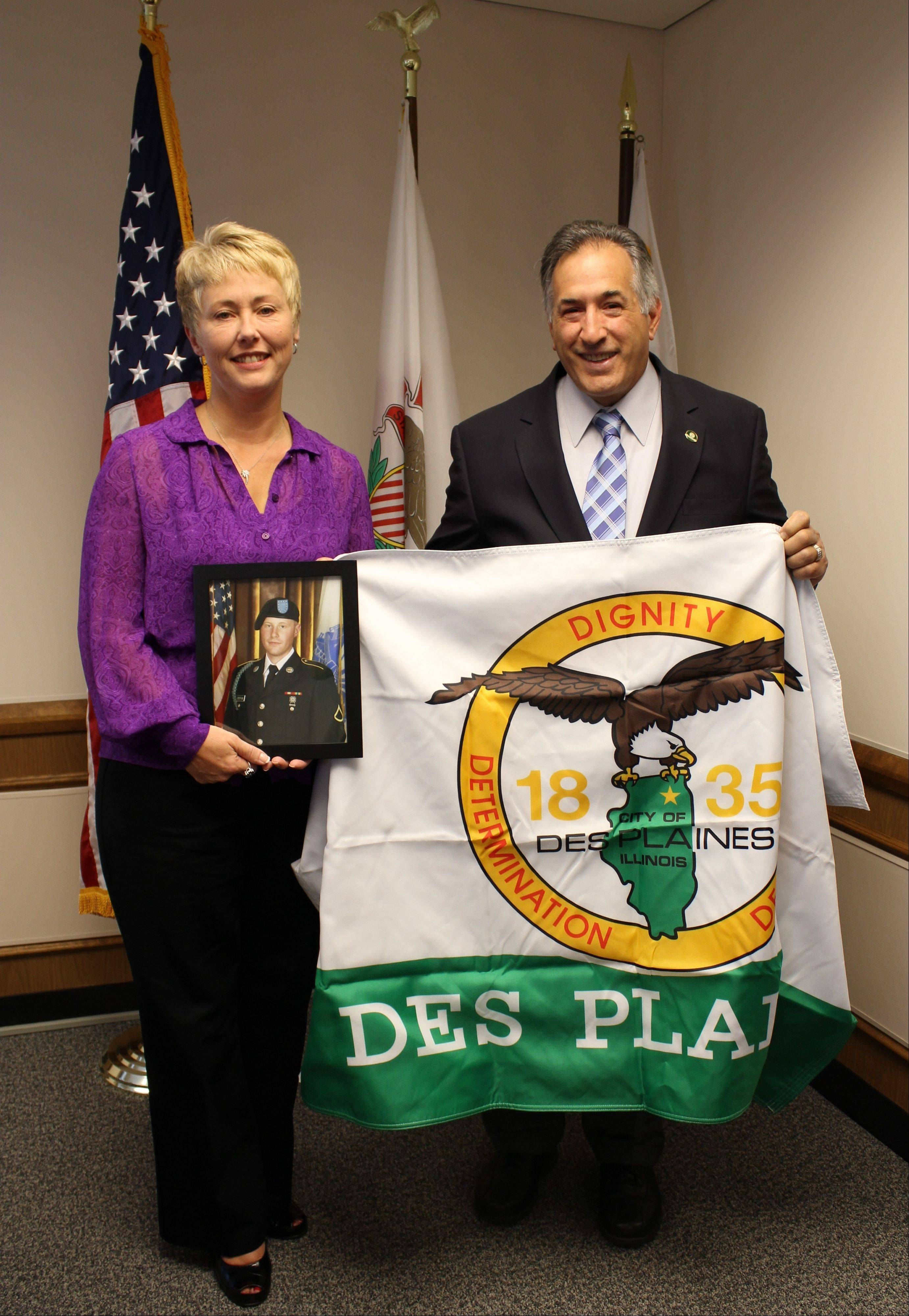 Resident Paula Steffan accepts a Des Plaines flag from Mayor Martin J. Moylan in the mayor�s office. Steffan will be sending the flag to her son, Jacob, serving in the Army in Afghanistan. Jacob joined the Army in 2010.