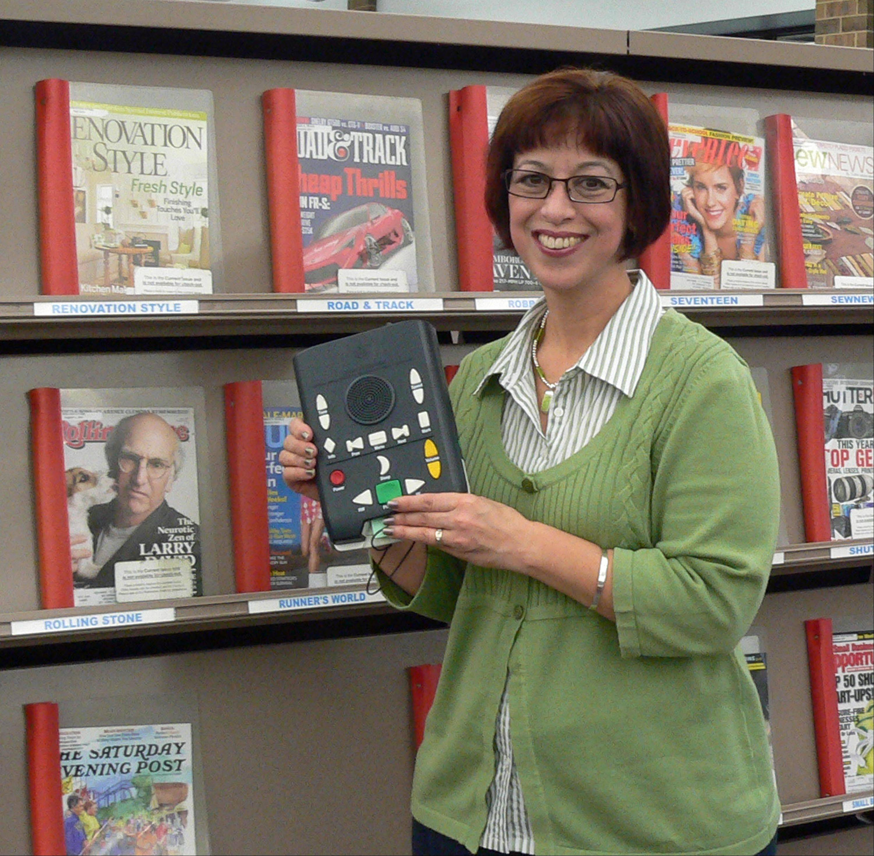 Vicki Ann Brodeur, coordinator of Naperville Public Library�s special services, shows the digital talking books device that allows the visually impaired and physically disabled to download books and magazines