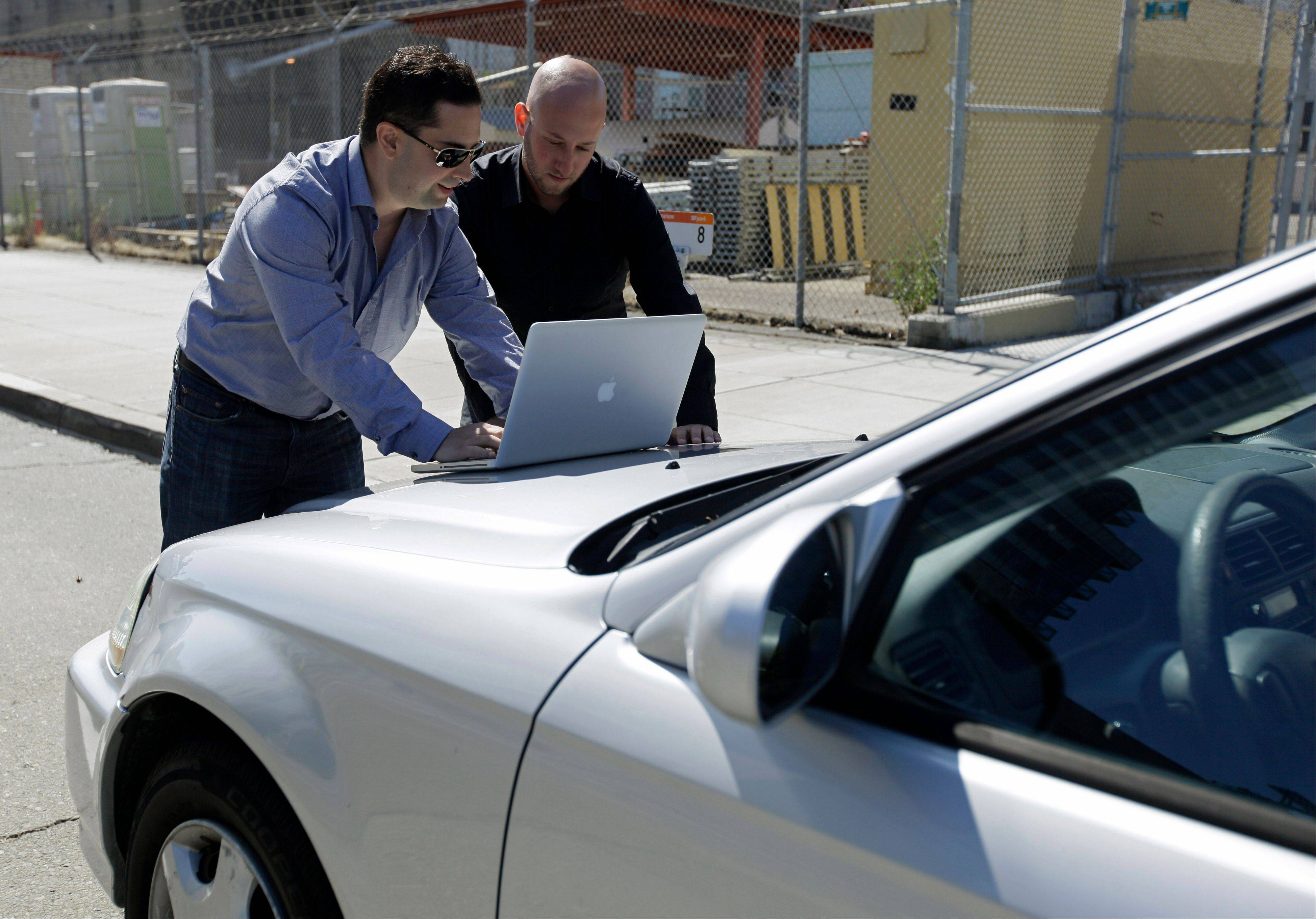 Security consultants Don Bailey, left, and Mathew Solnik, right, with iSEC Partners, demonstrate with a computer how they force cars with certain alarm systems to unlock their doors and start their engines by sending them text messages in San Francisco.