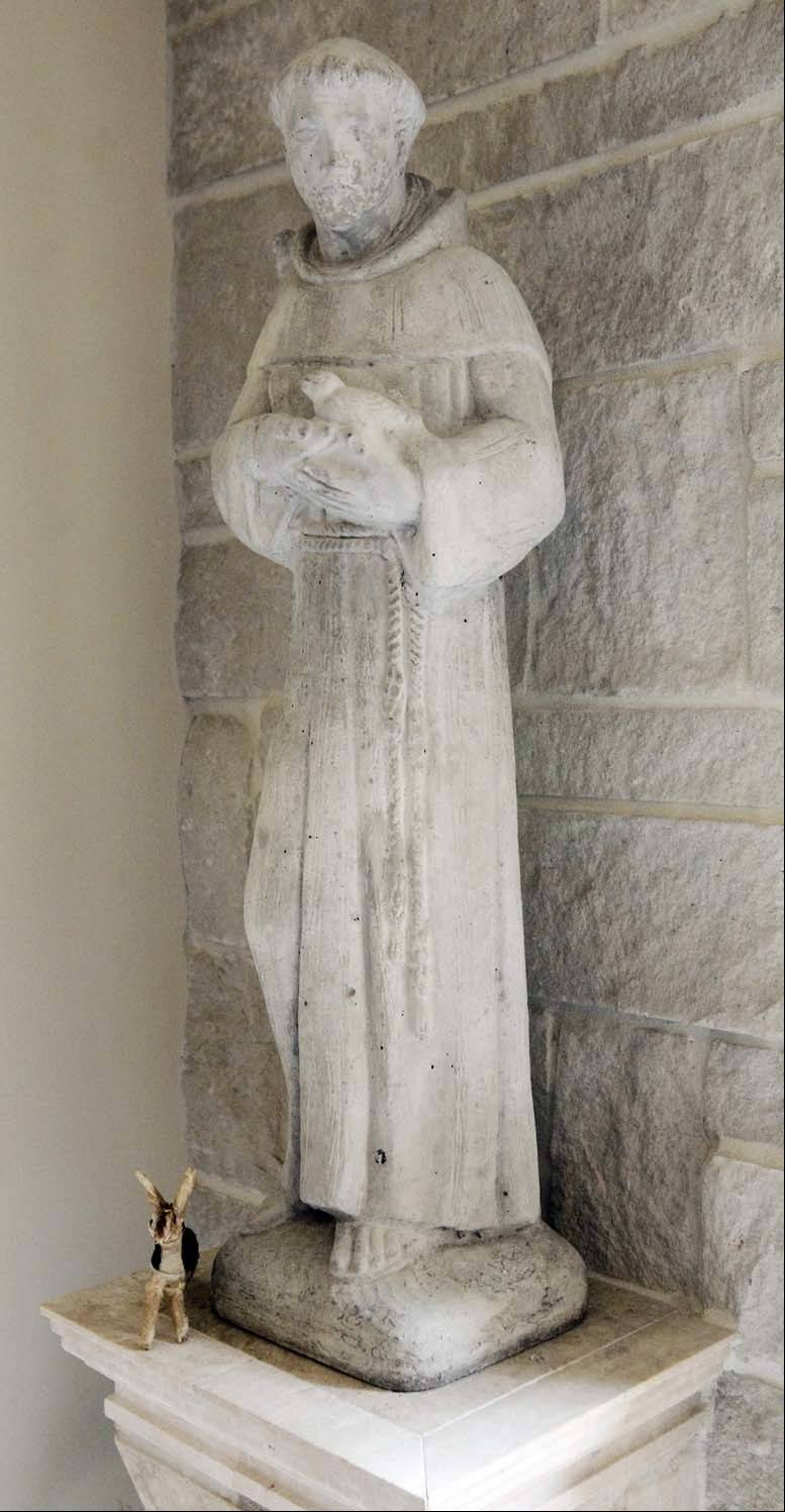 A weathered statue of St. Francis of Assisi dominates a corner of the chapel.