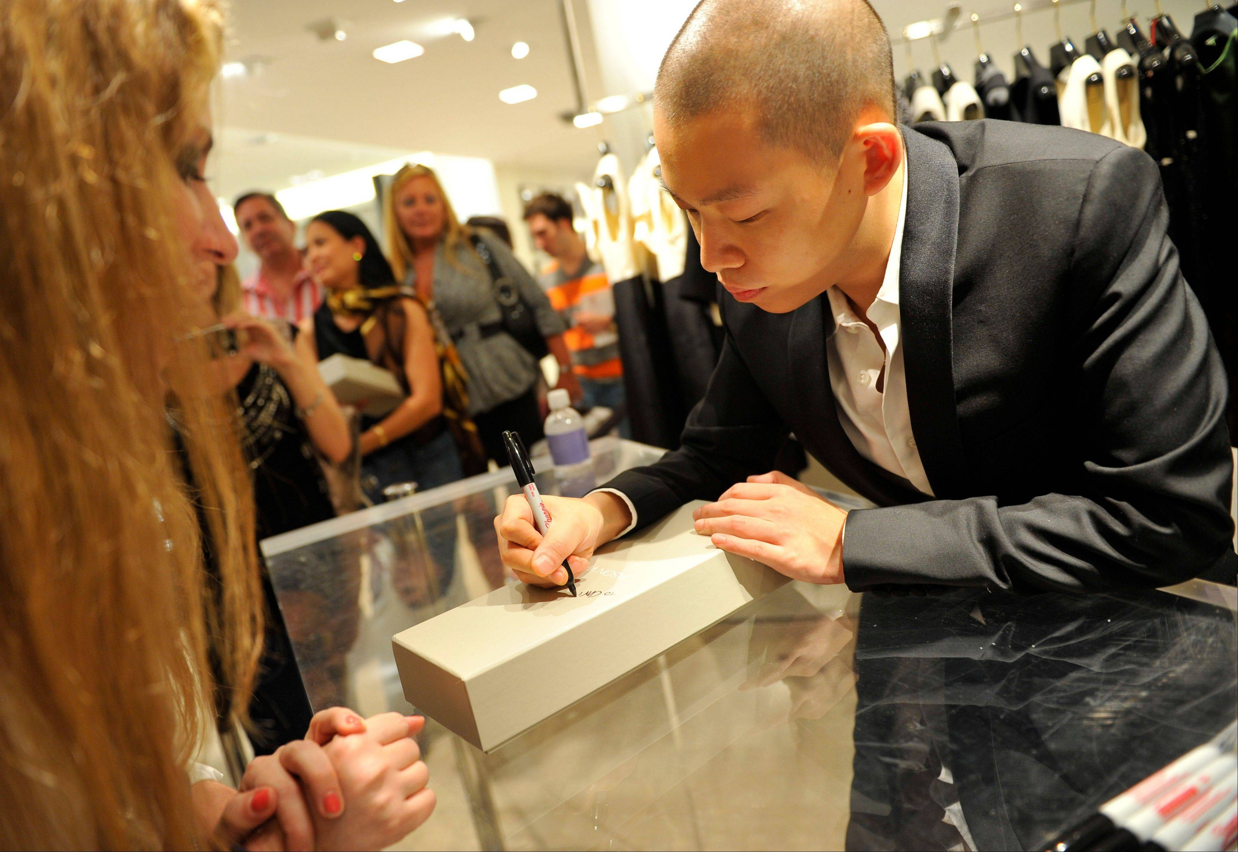 Designer Jason Wu autographs a box at Bergdorf Goodman during Fashion's Night Out during Fashion Week in New York last year.