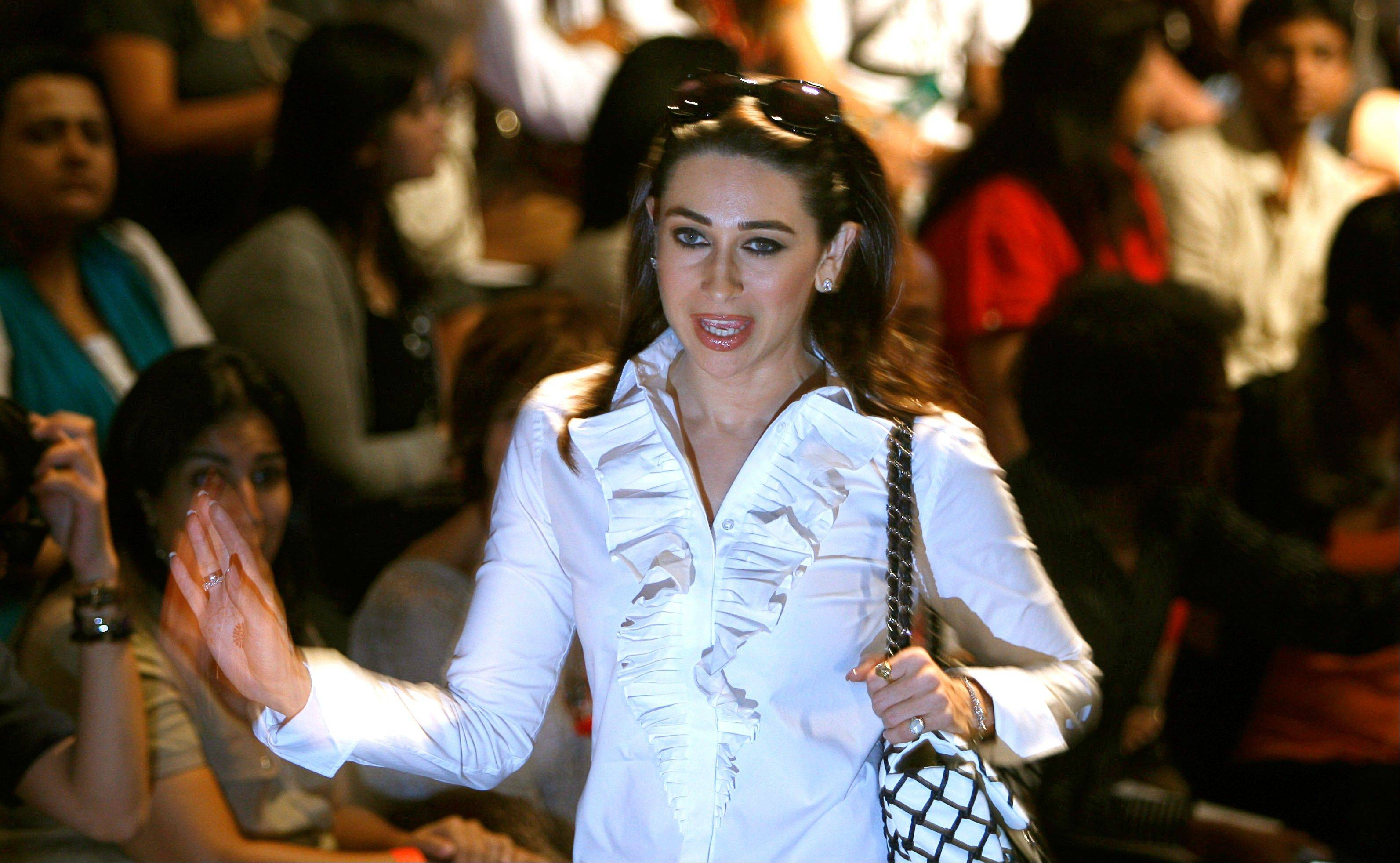 Bollywood actress Karisma Kapoor waves as she arrives to attend the Lakme Fashion Week in Mumbai, India.