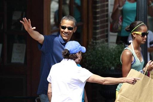 President Barack Obama, left, waves as he departs a book store with his daughters Malia Obama, right, and Sasha Obama, partially obscured behind center, in Vineyard Haven, Mass., on the island of Martha's Vineyard Aug. 19. Obama is vacationing on the island with his family during the last half of August 2011.