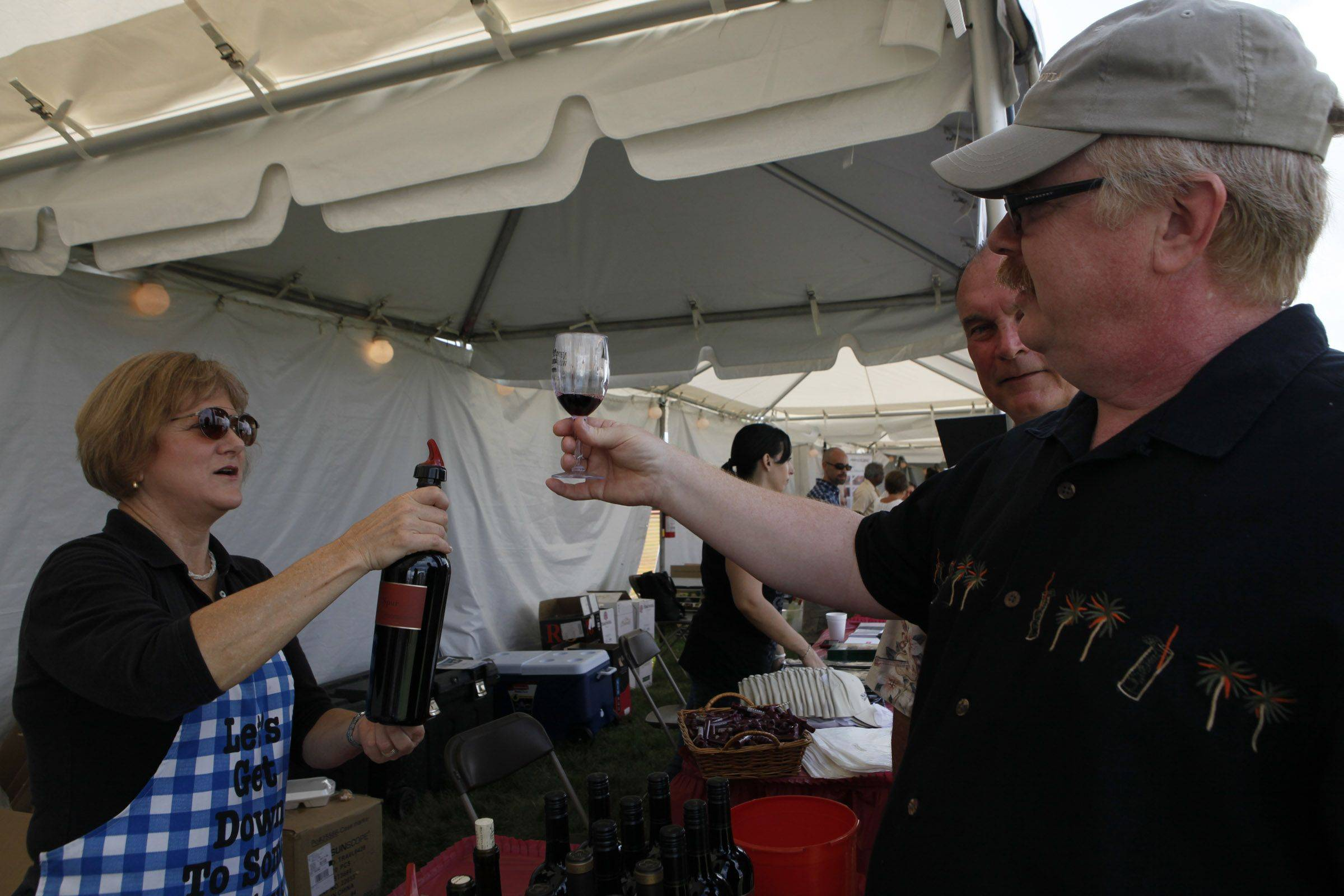 Bob Julian prepares to sample some wine from Lynne, who represents the Wente Estate, the oldest family-owned winery in North America, on Saturday at the Naperville Wine Festival at CityGate Centre.