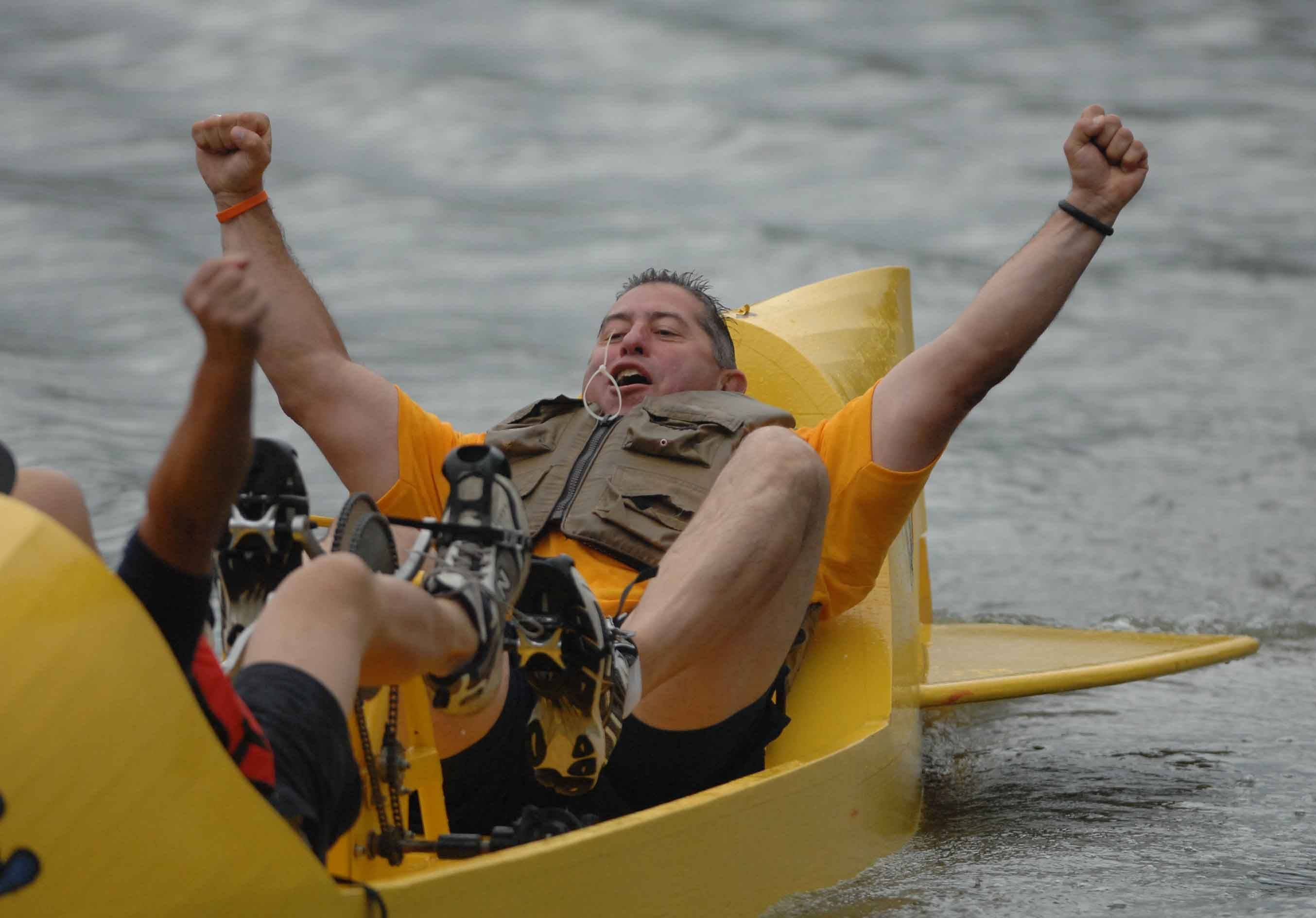 Kane County Sheriff Pat Perez throws his arms up in victory during the Fox Valley United Way's ninth annual What Floats Your Cardboard Boat Race Saturday on Mastodon Lake in Aurora's Phillips Park.