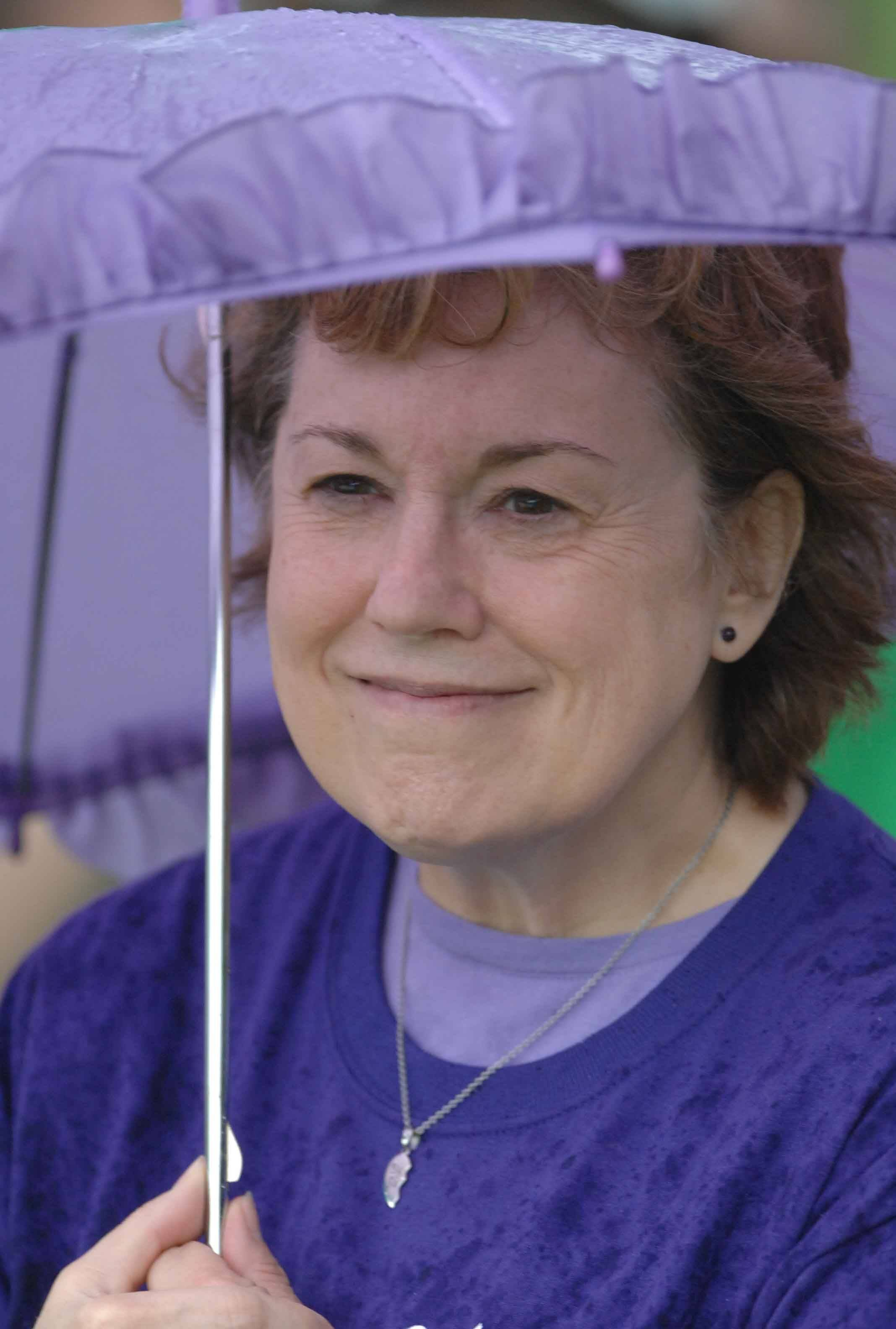Kim Carew of Aurora hides from the rain Saturday as she watches the ninth annual Fox Valley United Way What Floats Your Cardboard Boat Race on Mastodon Lake in Aurora's Phillips Park.