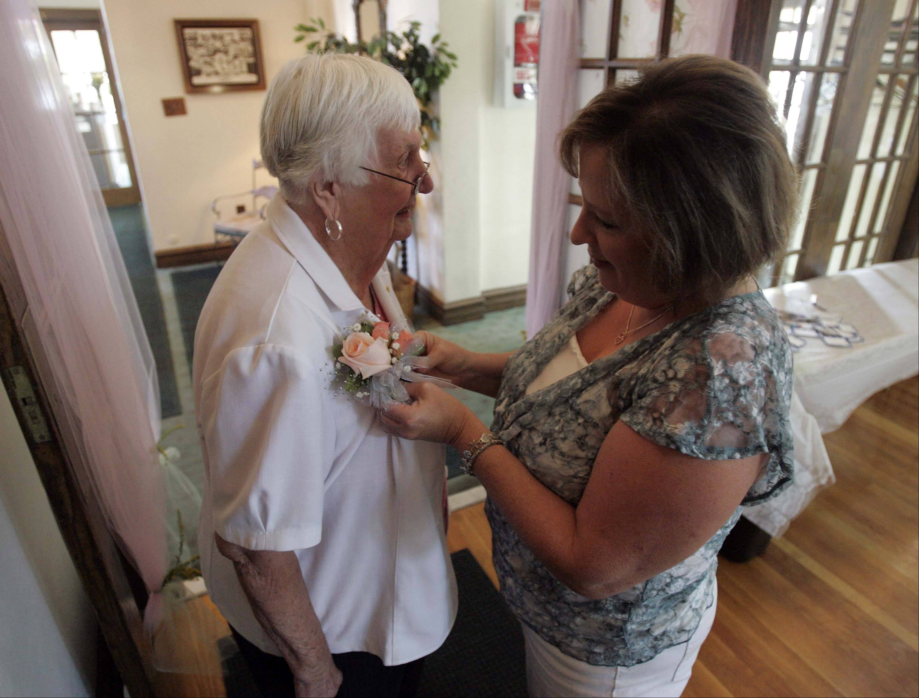 Co-worker Candy Boulay pins a corsage on Carol Glemza, 87, who is retiring after working 69 years for the St. Charles Park District.