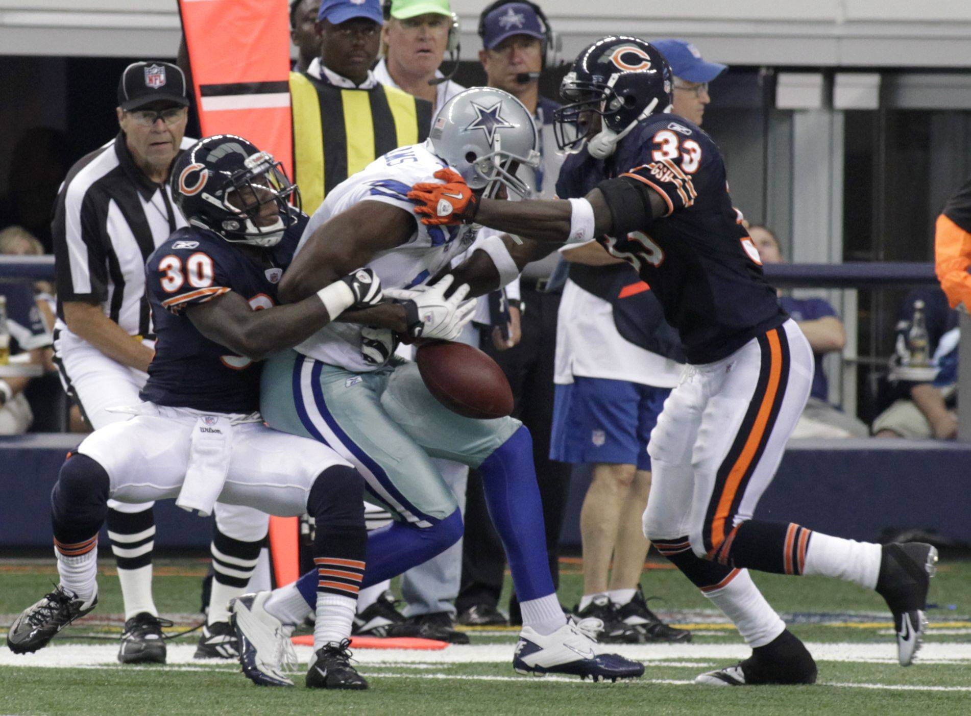 Chicago Bears cornerbacks D.J. Moore (30) and Charles Tillman (33) strip the ball from Dallas Cowboys wide receiver Roy E. Williams (11) late in an NFL football game, Sunday, Sept. 19, 2010, in Arlington, Texas. The Bears recovered the ball on the way to a 27-20 win.