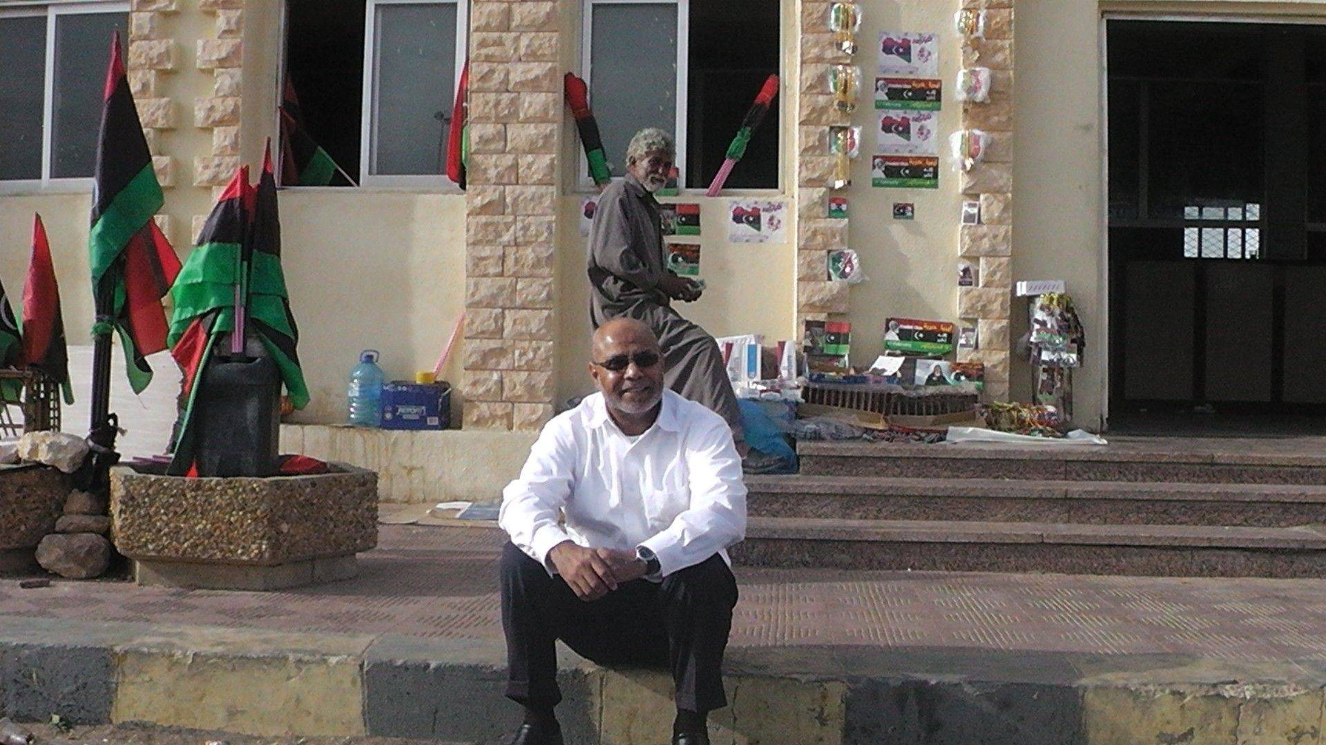 Ibrahim Mohamed sits on a curb in July at the Libyan border with Egypt before returning to his home city of Benghazi, Libya, for the first time in 31 years.