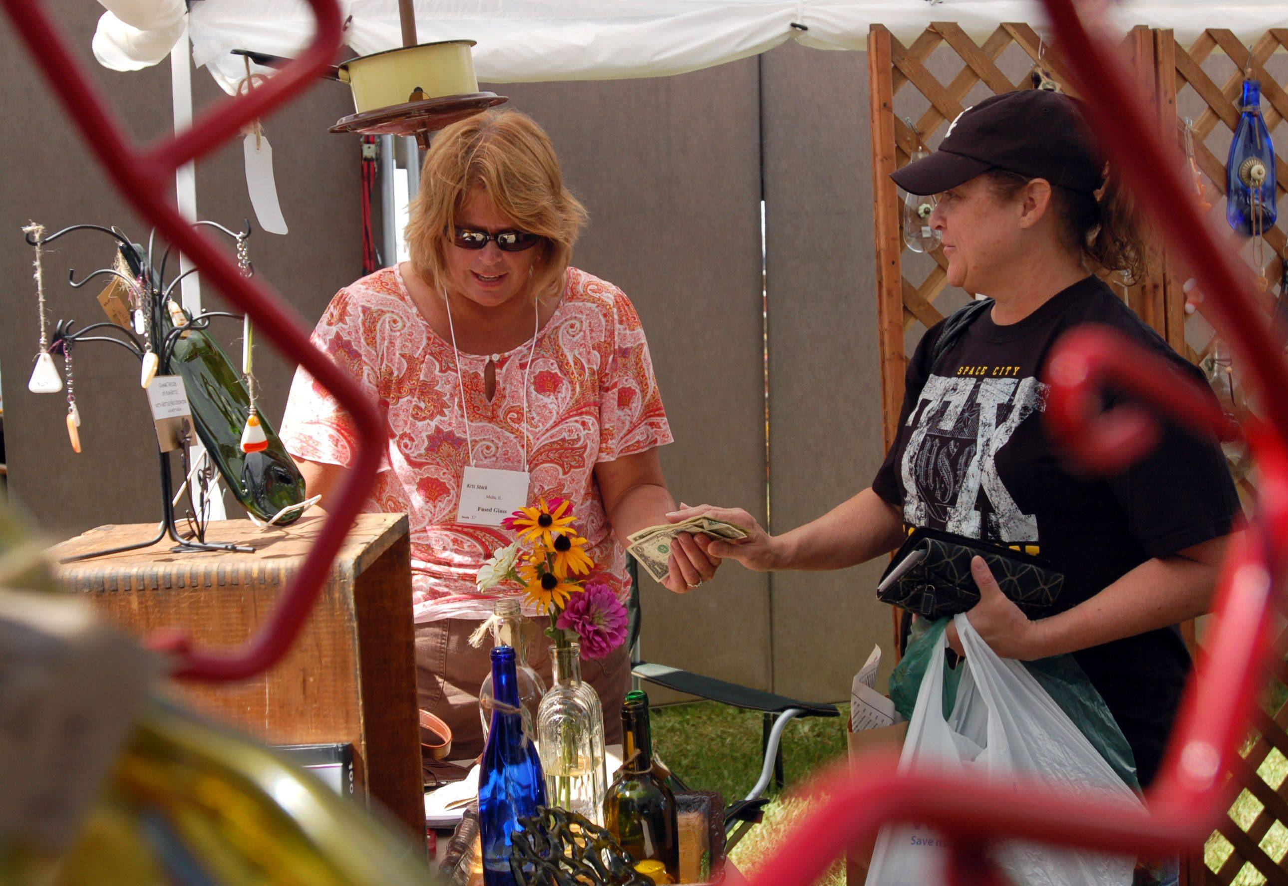 Kris Stark of Malta, left, sold one of her fused glass pieces to Paula Barden of Huntley, right, during the Huntley Artfest in downtown Huntley Sunday. Stark takes recycled glass objects and turns them into art.