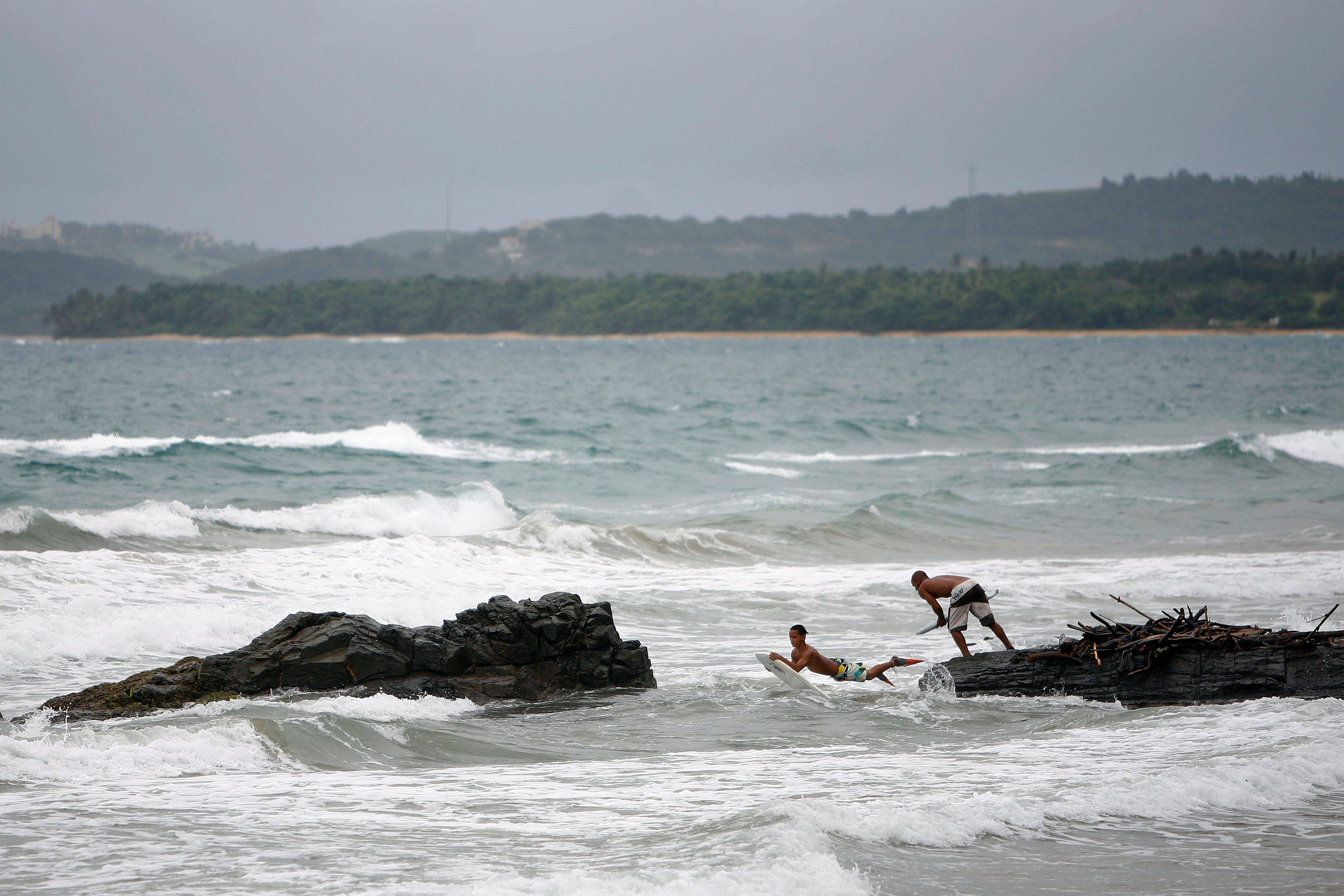 Surfers jump off the rocks into the ocean as Tropical Storm Irene approaches the island Sunday in Luquillo, Puerto Rico. The storm, packing winds of about 50 mph and tracking westward at 20 mph, was expected to strengthen and pass near the U.S. island of Puerto Rico later Sunday or early Monday.