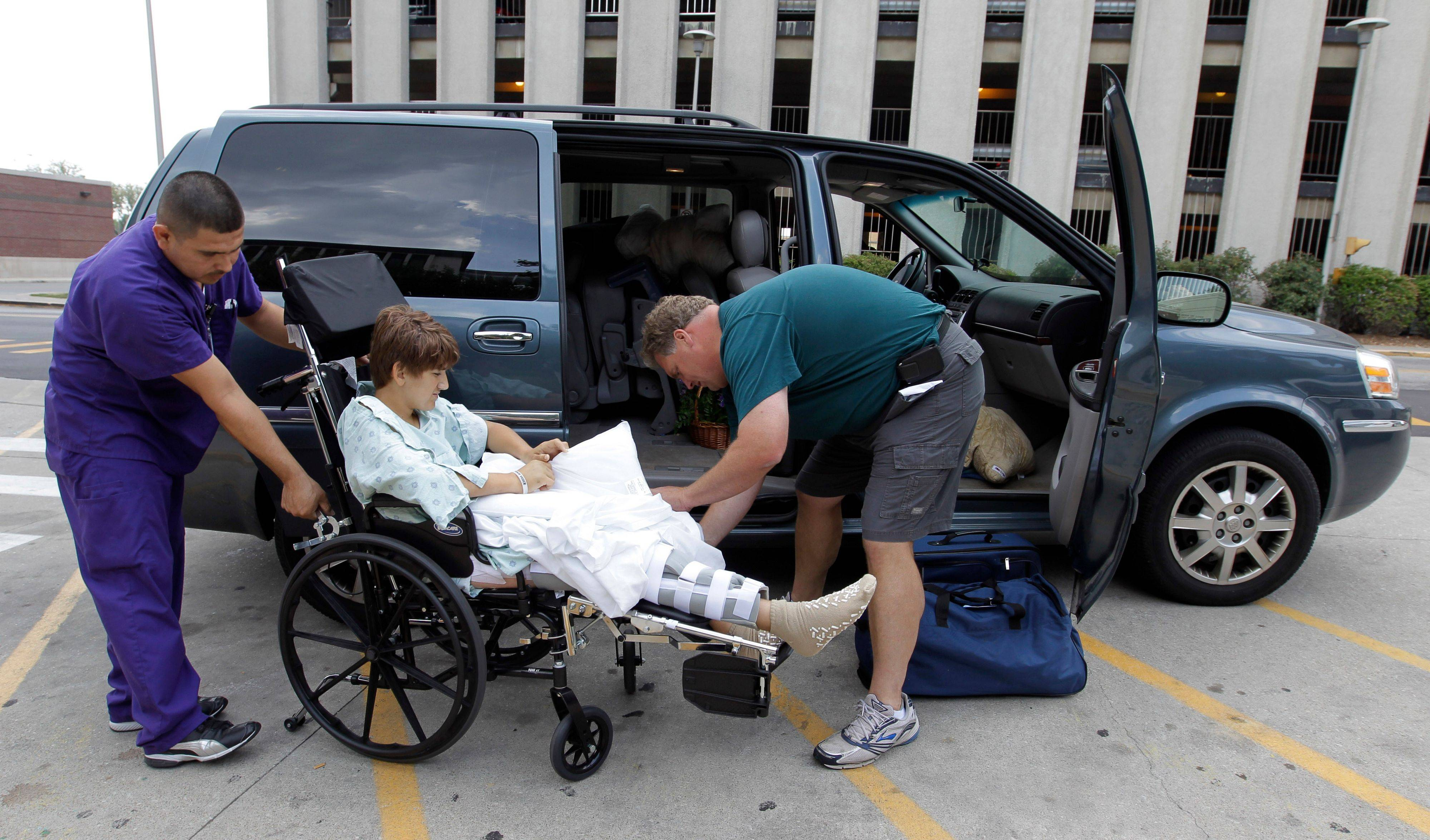 Tim Brunn, of Island Lake helps his son Josh into their van after he was released from Riley Hospital for Children in Indianapolis. Josh, along with his mom, Karen, were injured when a stage collapsed at the Indiana State Fair last week. Personal Service Assistant Irwing Rivera helps the Brunns.