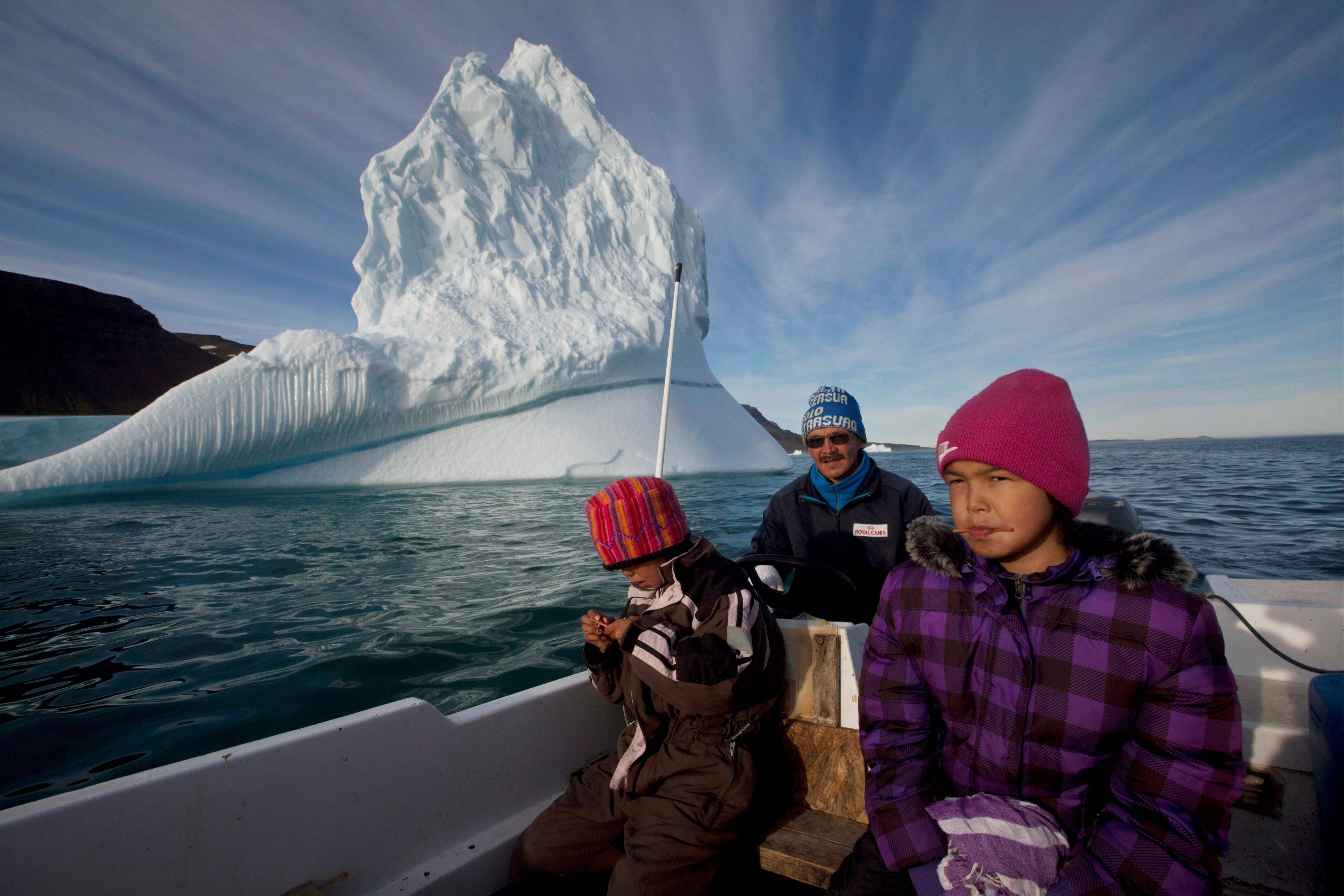 Inuit hunter Nukappi Brandt steers his small boat as he and his daughter Aaneeraq, 9, scan the water for seals, accompanied by his other daughter Luusi, 8, outside Qeqertarsuaq, Disko Island, Greenland. Brandt, 49, has been a hunter since age 14, and said roughly 20 years ago, when winter sea ice became too thin to support dogsleds, seal hunting ceased to be a sustainable way of life here.