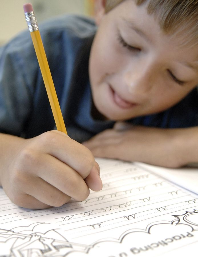 Luke Bellizzi, 8, practices the letter 'U' in cursive in Aleta Piper's class third-grade class at Liberty Elementary School in Carpentersville.