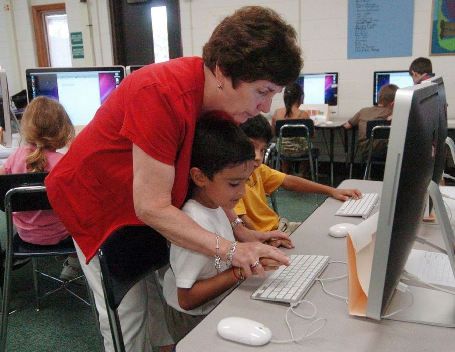Learning Resource Center teacher Eileen Justus helps a student out on his technique as kids learn keyboarding in the library at the Ridge Family Center for Learning in Elk Grove Village.