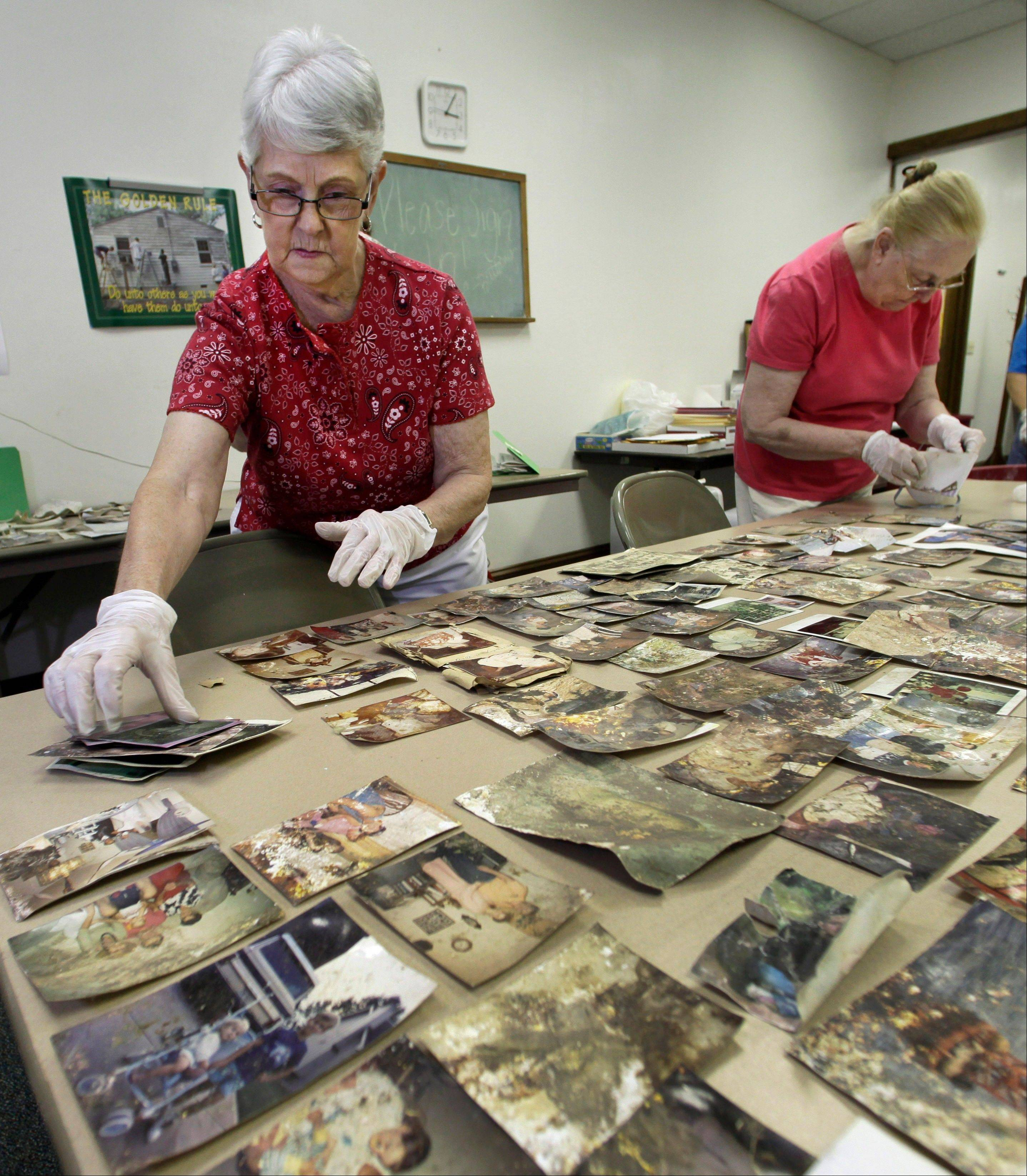 Margaret Hagenbaumer, left, and Martha Cardwell, volunteers at the First Baptist Church in Carthage, Mo., clean and sort photos and other personal documents found among rubble after a powerful EF-5 tornado destroyed a large swath of nearby Joplin, Mo. on May 22, 2011. The church has taken on the task of preserving thousands of lost photos and reuniting them with their owners.