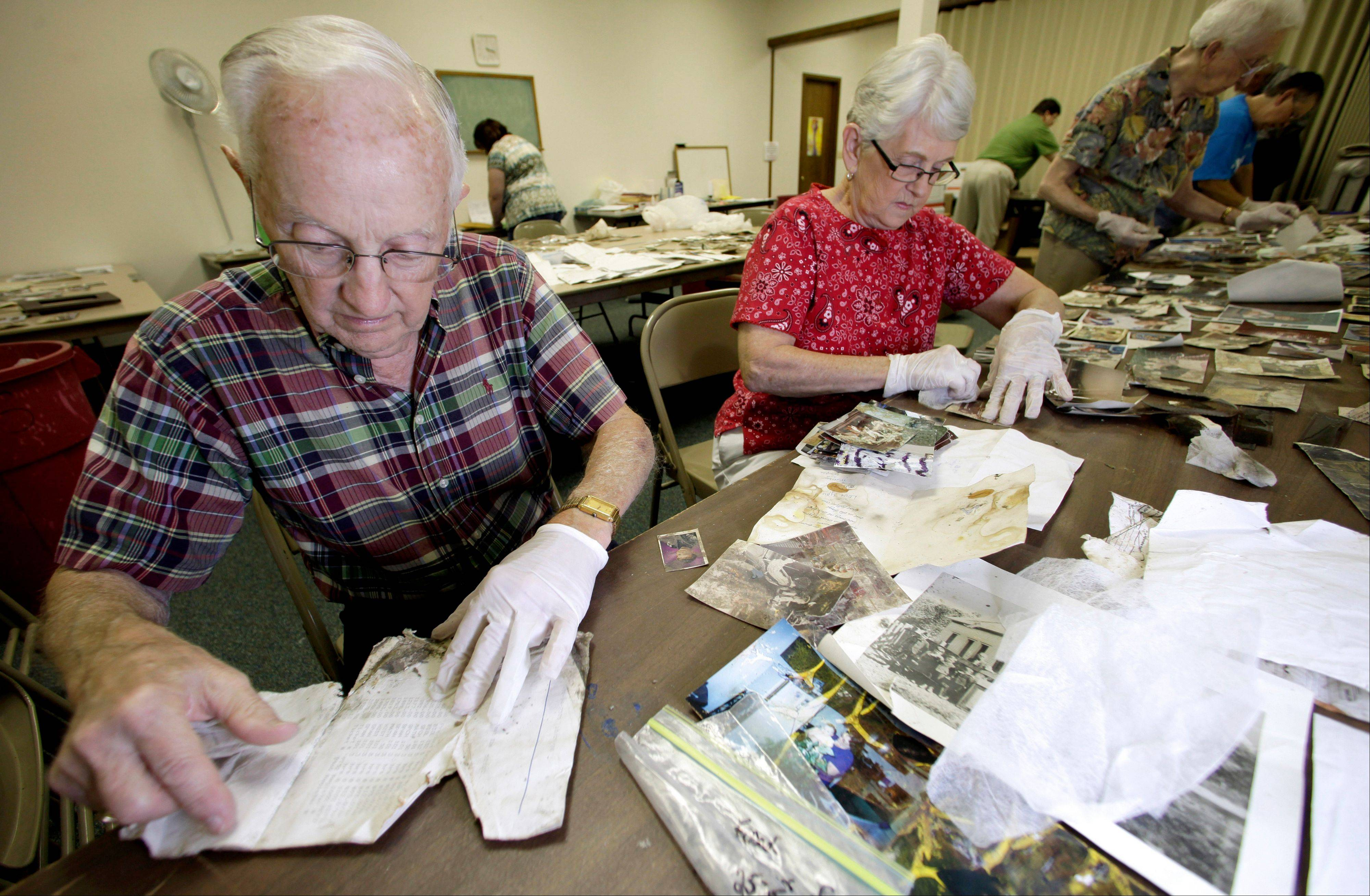 Glenn and Margaret Hagenbaumer, volunteers at the First Baptist Church in Carthage, Mo., clean and sort photos and other personal documents found among rubble after a powerful EF-5 tornado destroyed a large swath of nearby Joplin, Mo. on May 22, 2011. The church has taken on the task of preserving thousands of lost photos and reuniting them with their owners.
