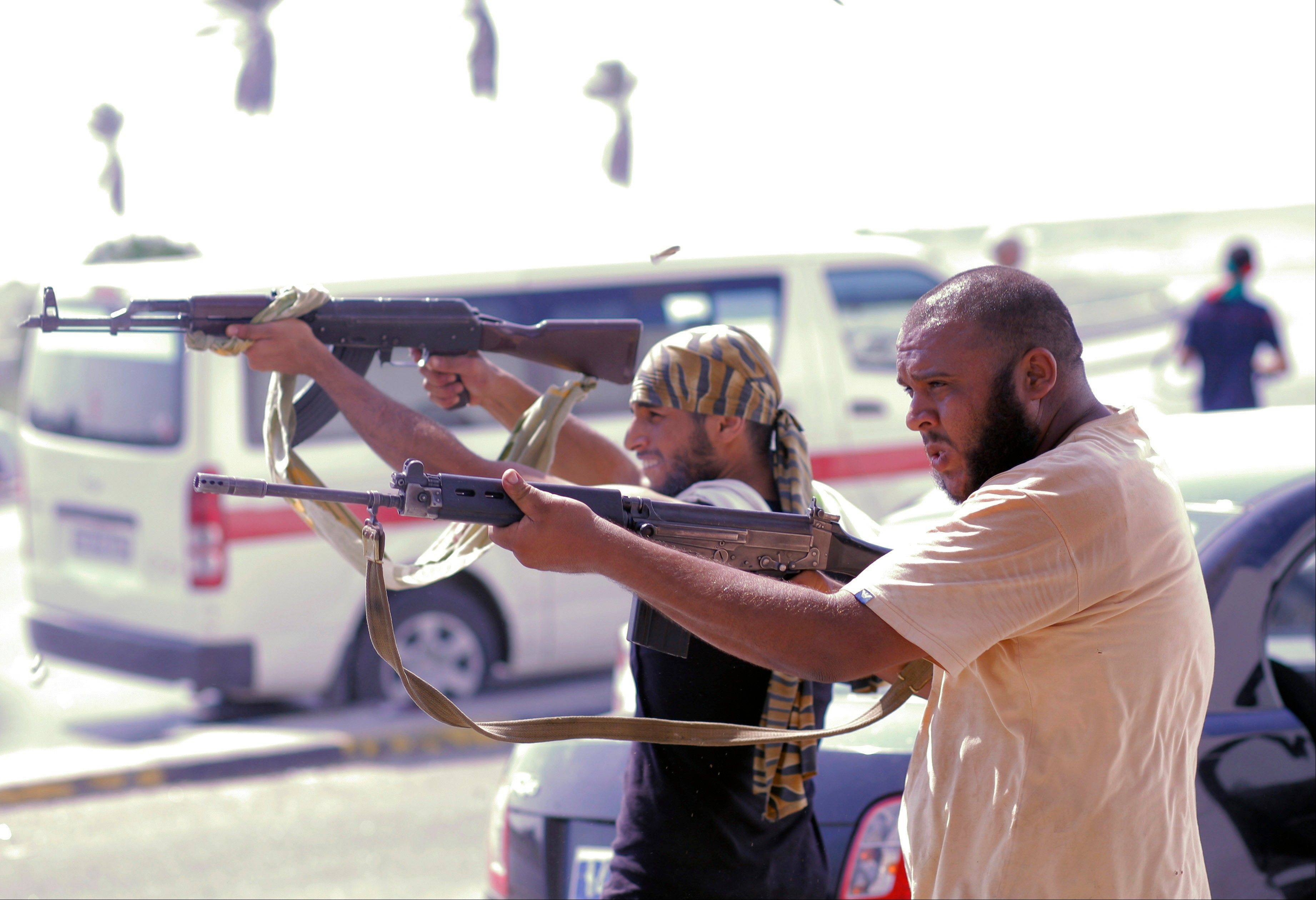 Libyan rebel fighters shoot towards pro-Gadhafi forces during fighting in downtown Tripoli, LIbya, Monday, Aug. 22, 2011.