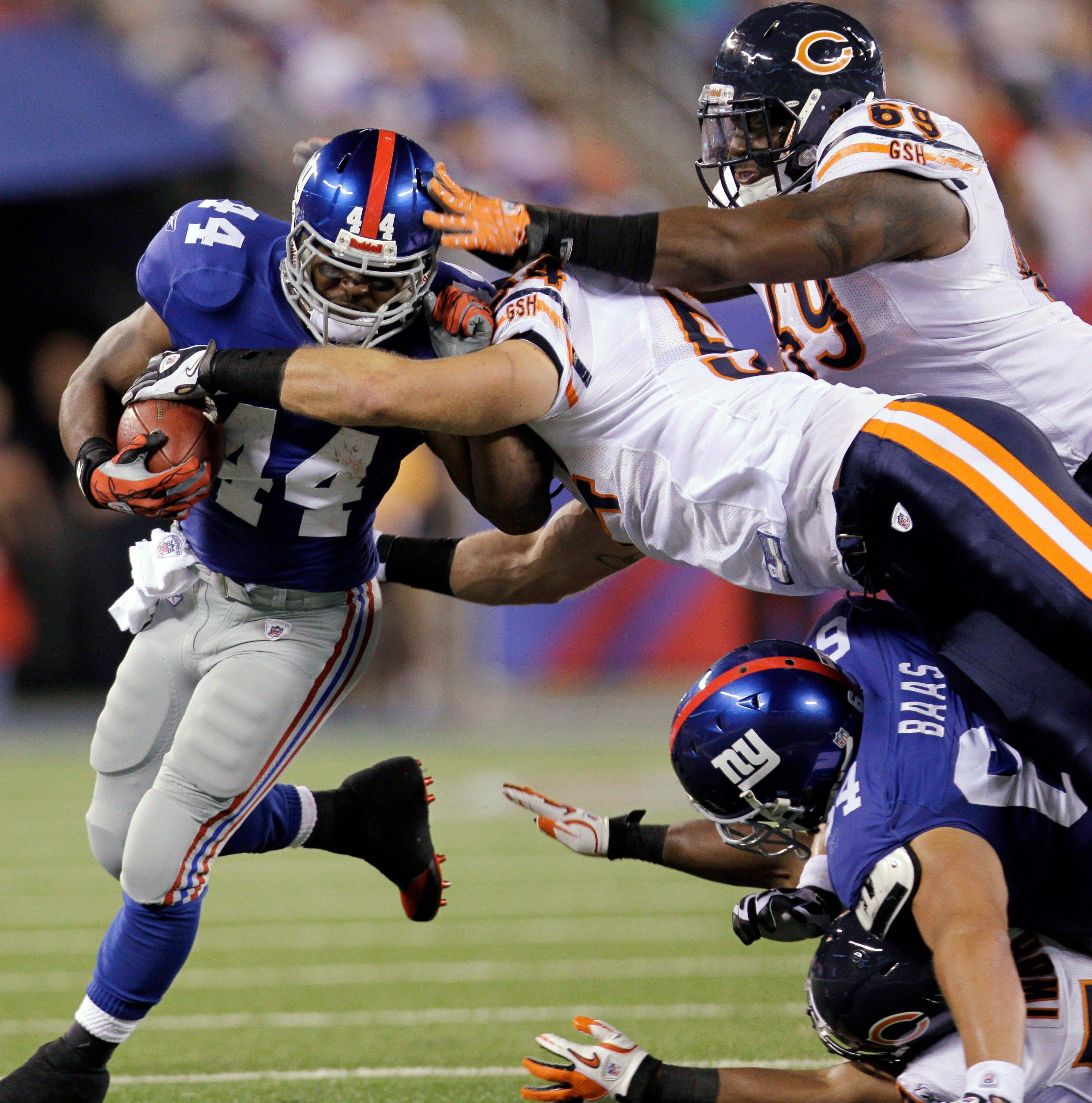 New York Giants running back Ahmad Bradshaw gets past the Bears� Brian Urlacher (54) and Ricky Henry (69) during Monday�s first quarter at the Meadowlands.