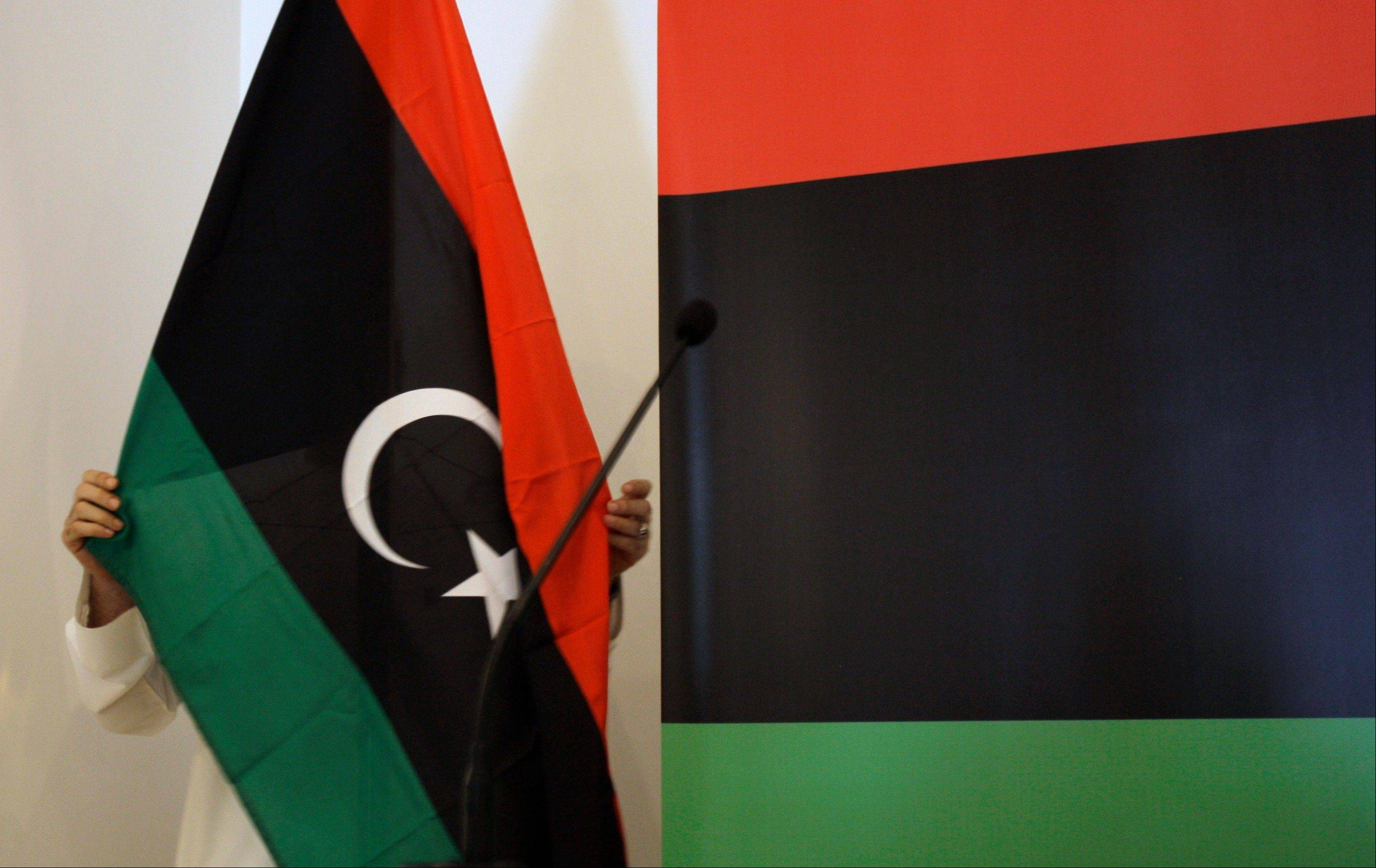 Libyan Abdulhakim Abouabdalla fixes the rebel flag before a press conference at the Libyan consulate in Dubai, United Arab Emirates, Sunday. Oil prices should fall in the next several months.