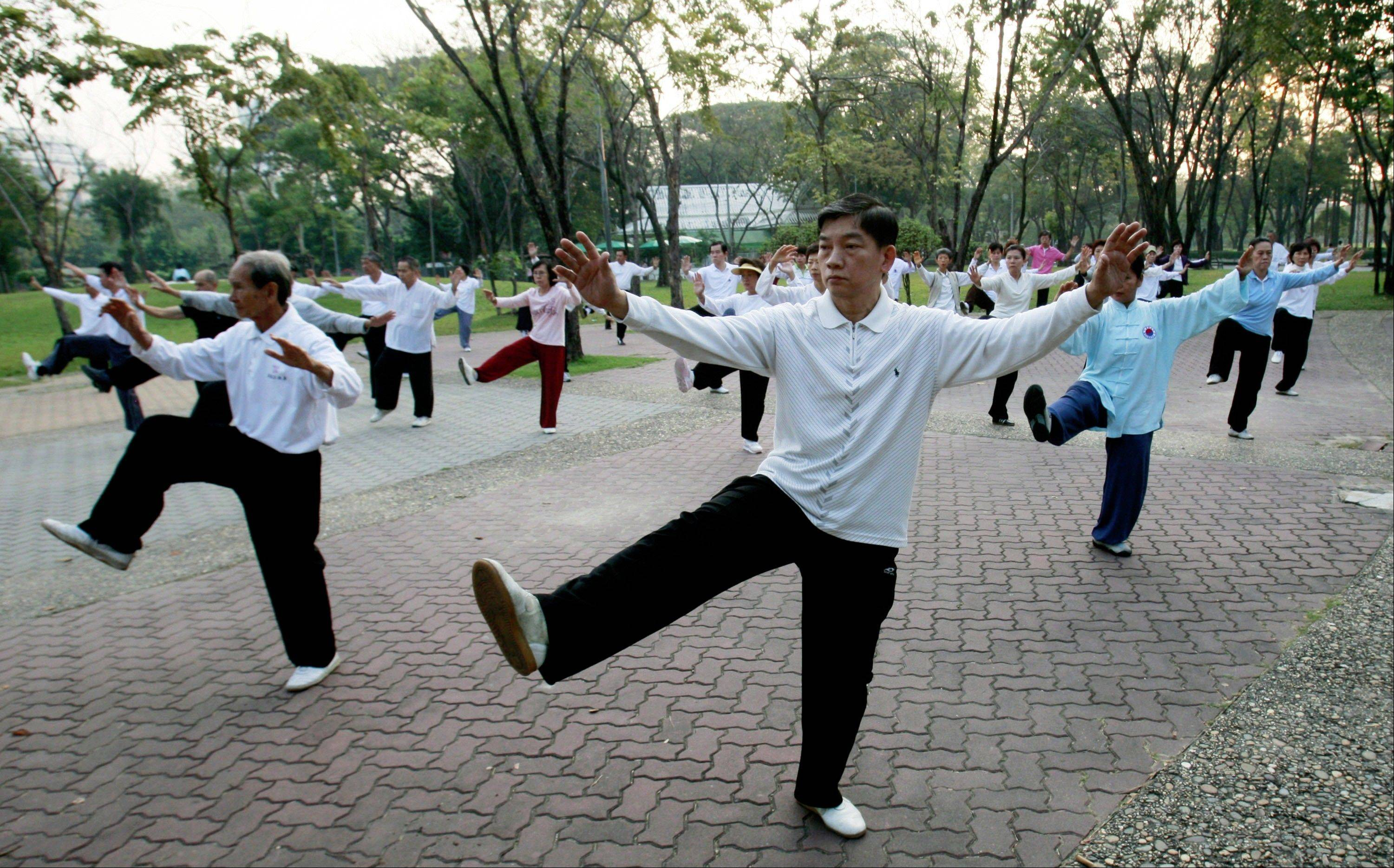 Thai-Chinese men and women perform morning exercises by practicing Chinese martial arts at a park in Bangkok, Thailand. New research concludes that even 15 minutes of moderate exercise like brisk walking can add years to your life.