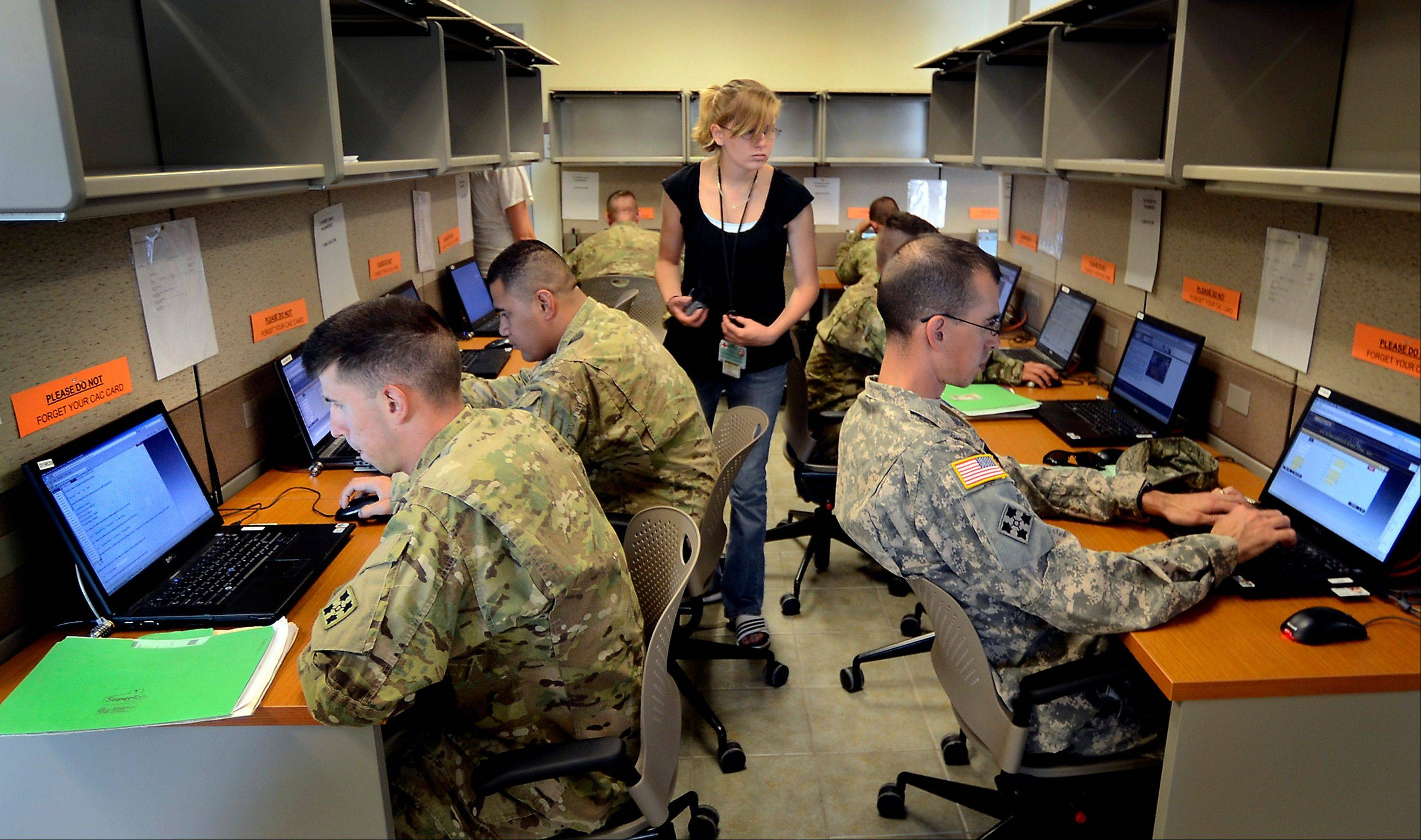Soldiers from the 4th Infantry Division are evaluated during a cognitive testing exercise to help determine if they suffer from TBI. Red Cross volunteer Shelly Horner, center, helps with questions.