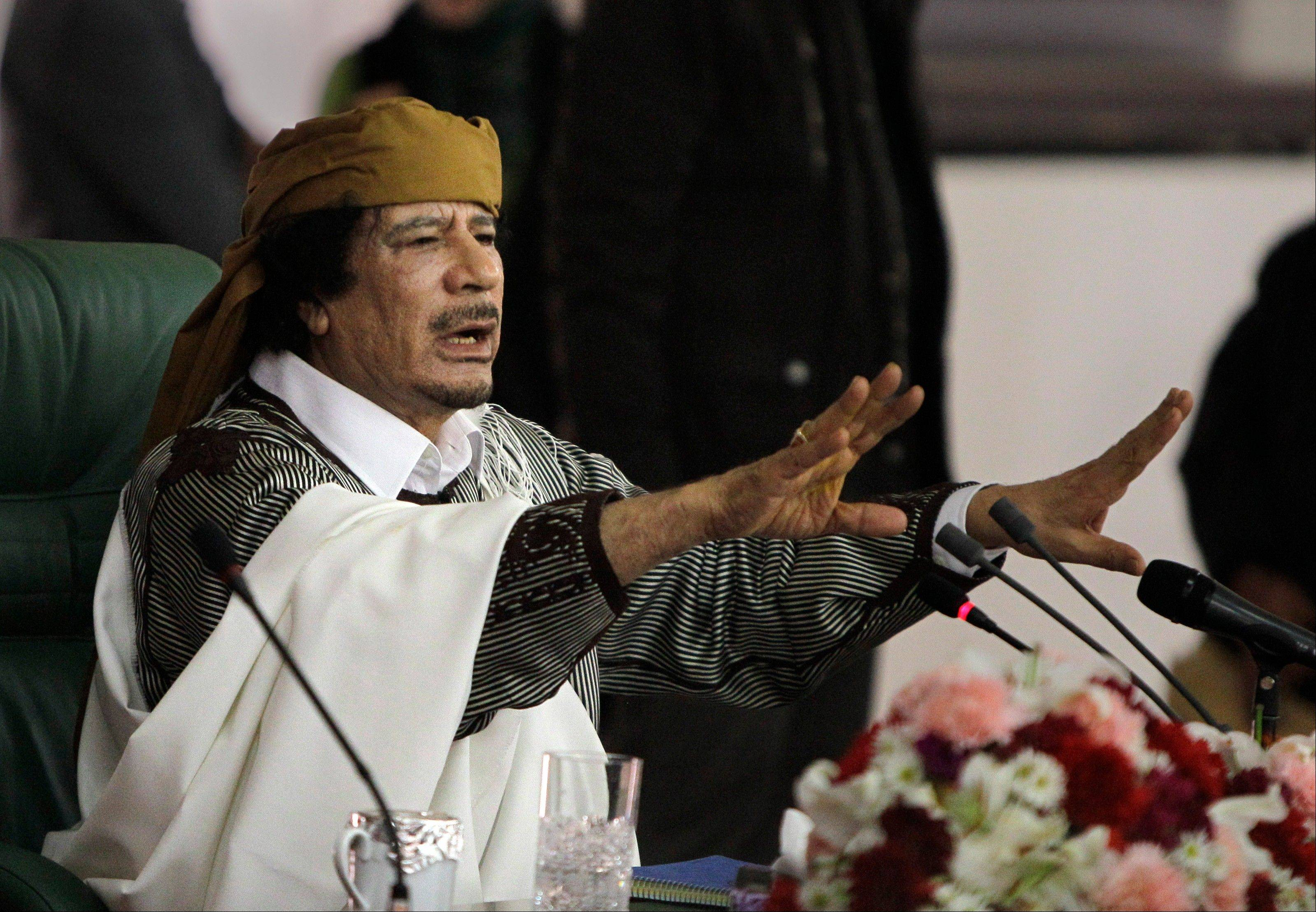 In this March 2, 2011 file photo, Libyan Leader Moammar Gadhafi gestures to supporters as he speaks in Tripoli, Libya.