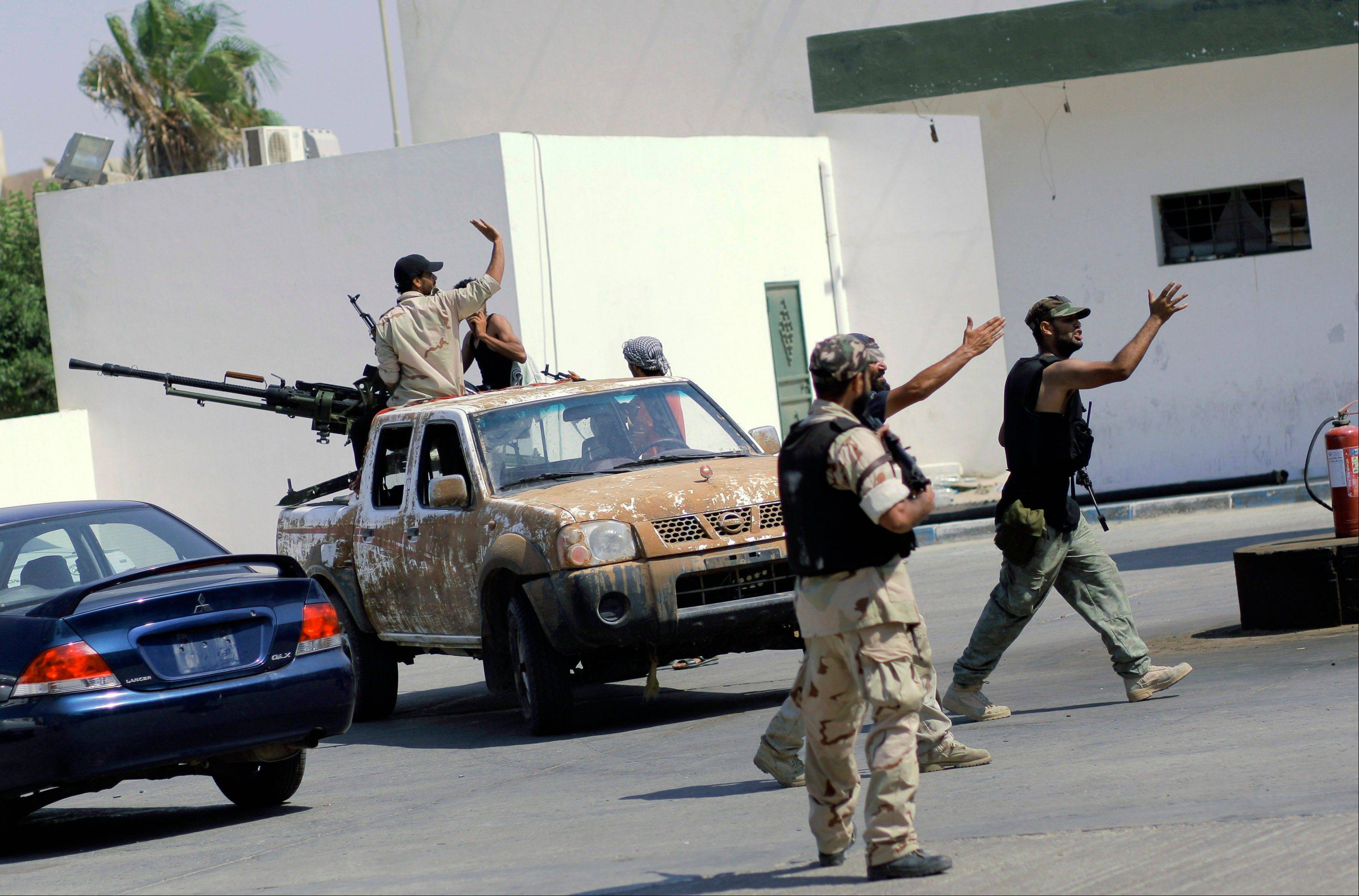 Libyan rebel fighters gesture during fighting in downtown Tripoli.