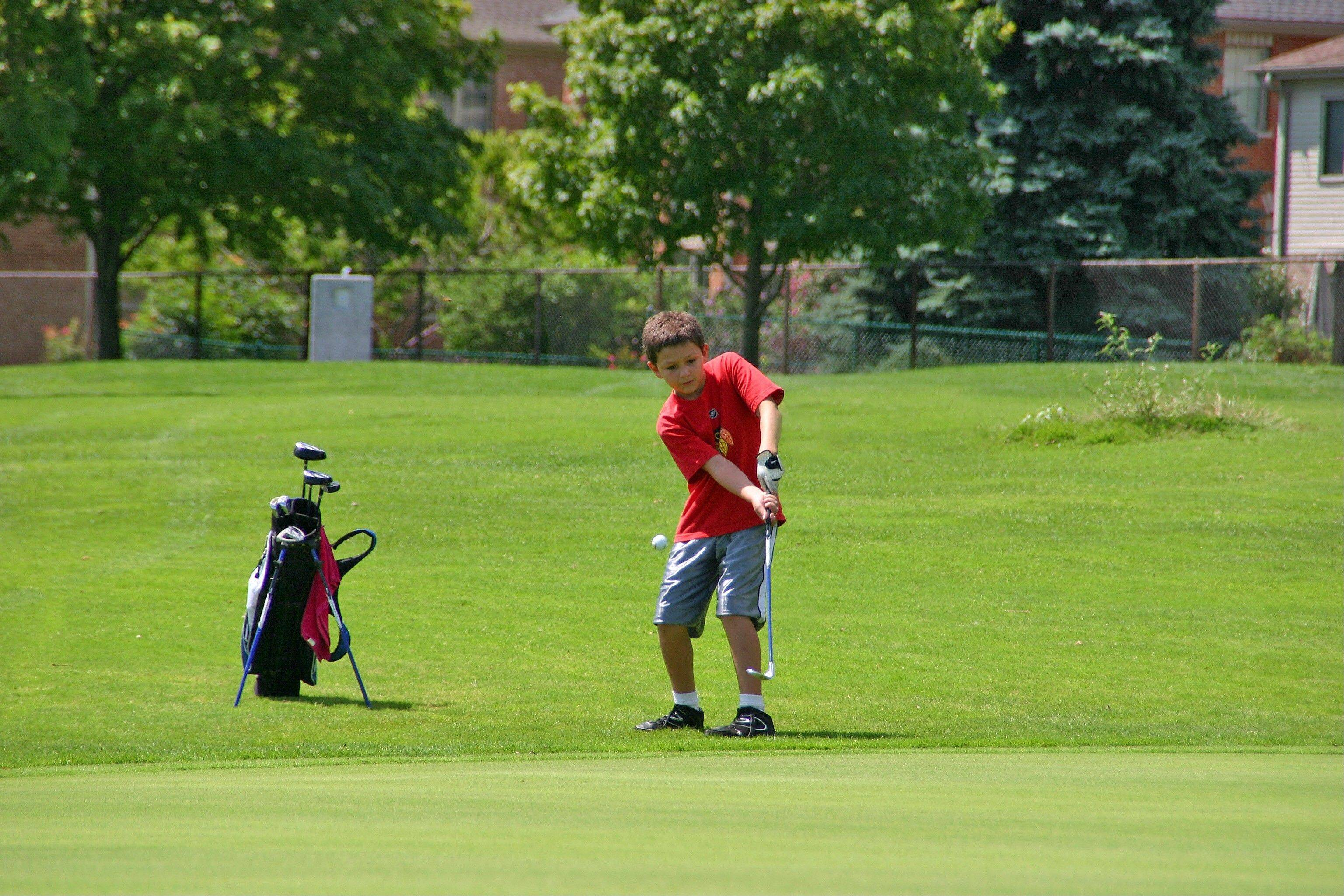 A young golfer chips onto the green at the eighth annual Optimist Club Youth Golf Outing at Lake Park.